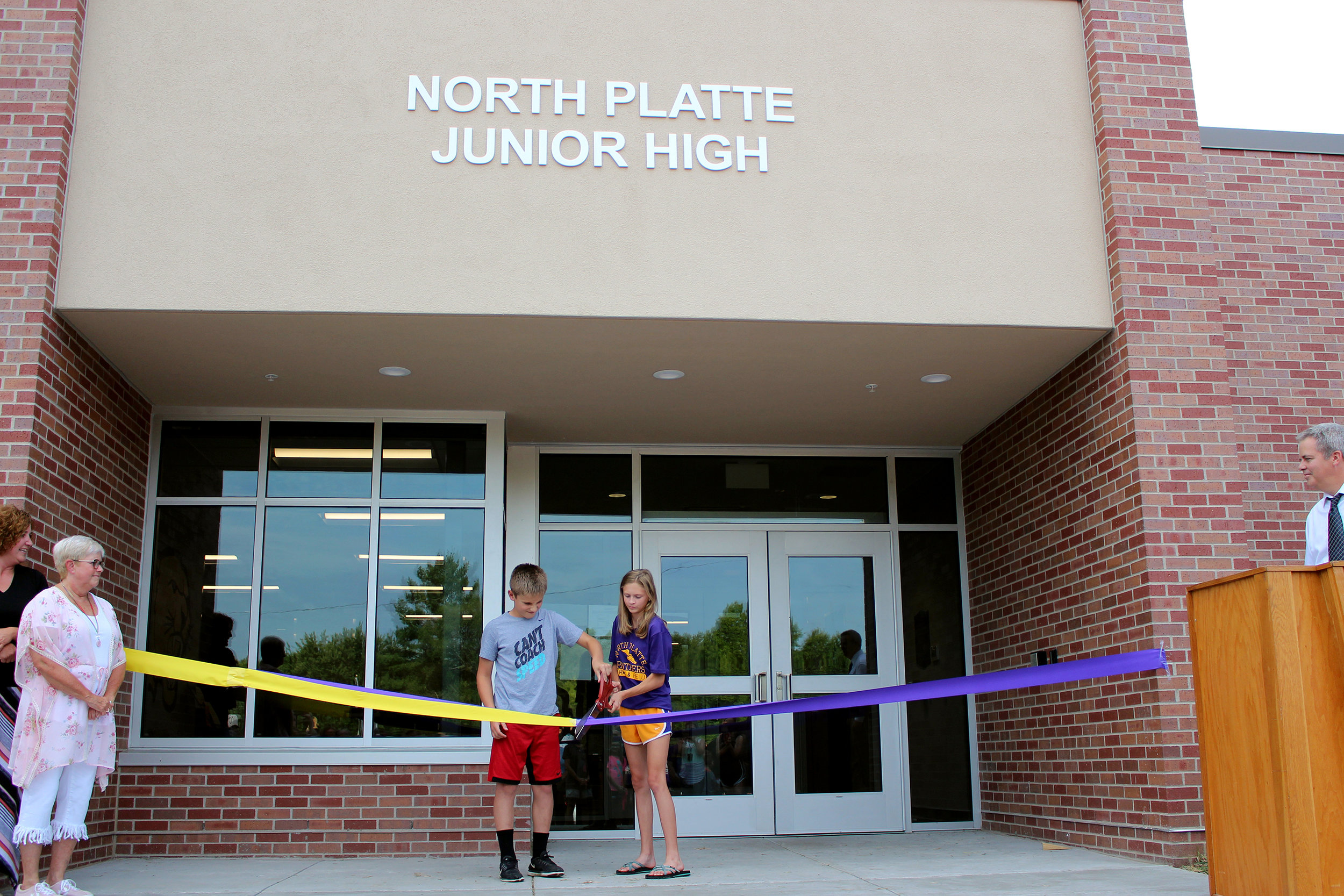 CODY THORN/Citizen photo North Platte sixth grader Ashton Shepardson, left, and Olivia Rogers, an eighth grader, cut the ceremonial ribbon placed in front of the new entrance for the North Platte Junior High. A $6.65 million dollar construction project saw portions of the building, first constructed in 1930, undergo extensive renovations. The ribbon cutting was held 10 days before the start of school.