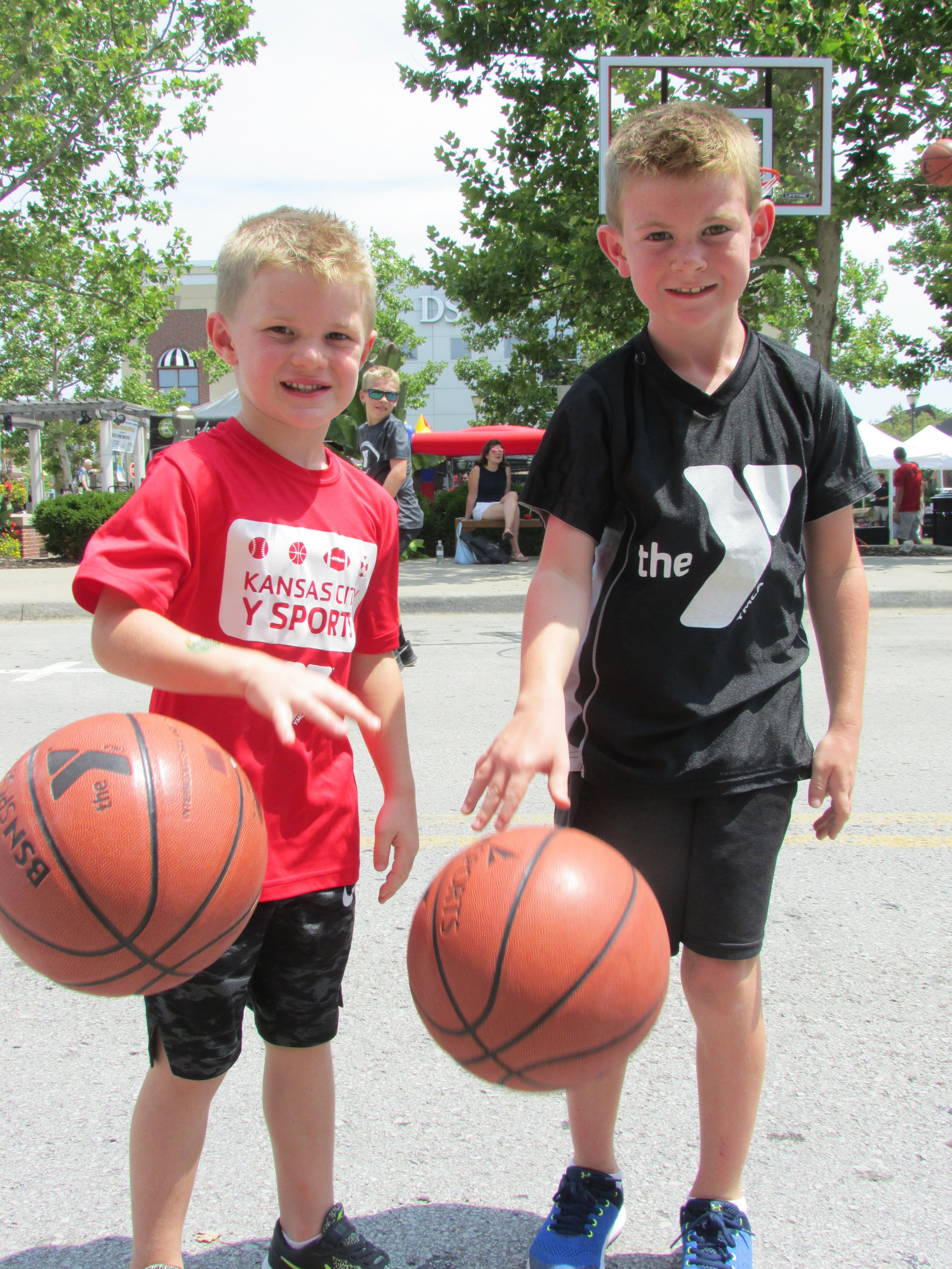 KALEB HUFFMAN/ Special to the Citizen  Riverside residents Thatcher Farrow, 5, left, and Broderick Farrow, 8, dribble a basketball during the 4th annual Platte County Sports Commission Youth Sports Festival held on Saturday Aug. 4 at Zona Rosa Town Center.