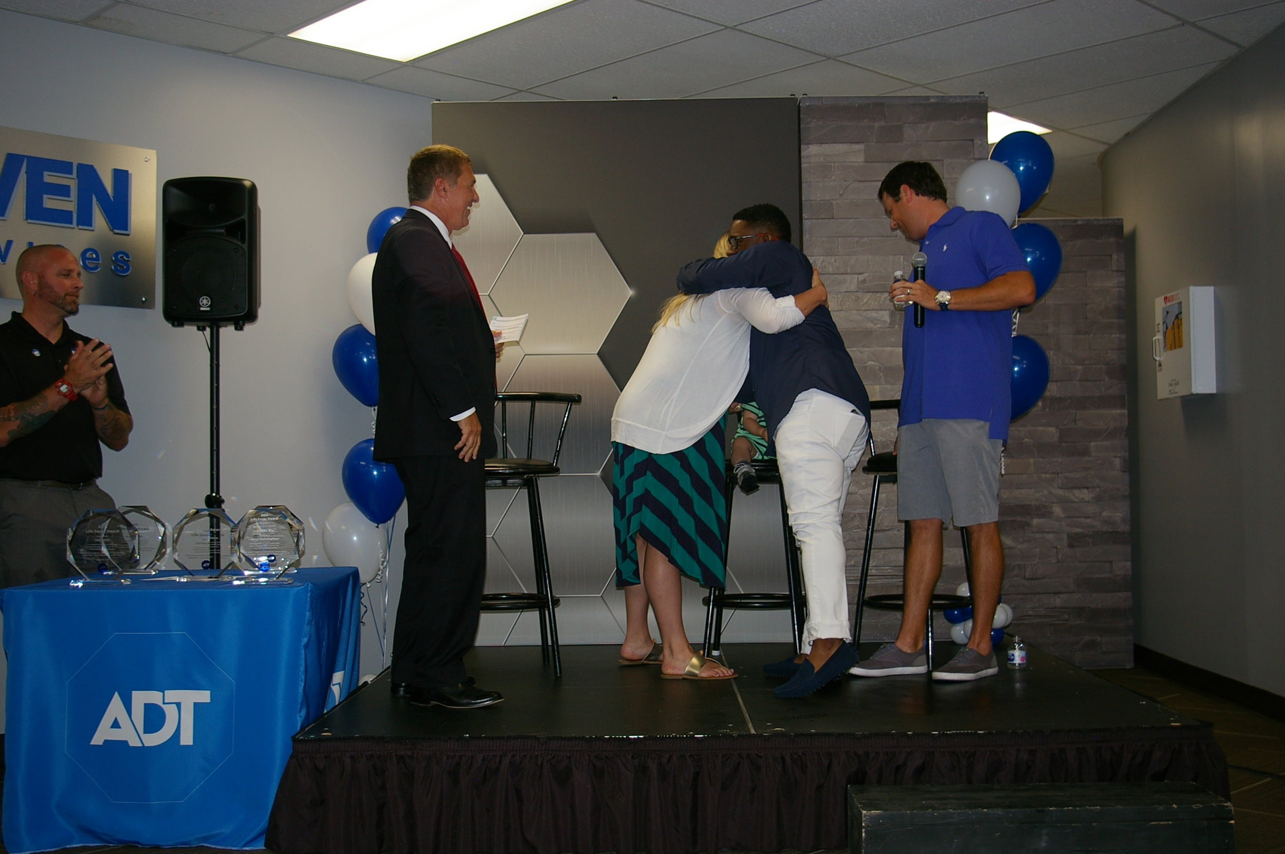 Jeanette Faubion/Citizen photo Kayla and Lee Hoffman of Parkville greet ADT dispatcher Jamar Cunningham (center) with a hug at a Life Saver Program award ceremony last week in North Kansas City. Cunningham was flown in from Florida to receive an award from ADT president of dealer partnerships Joe Nuccio, far left.