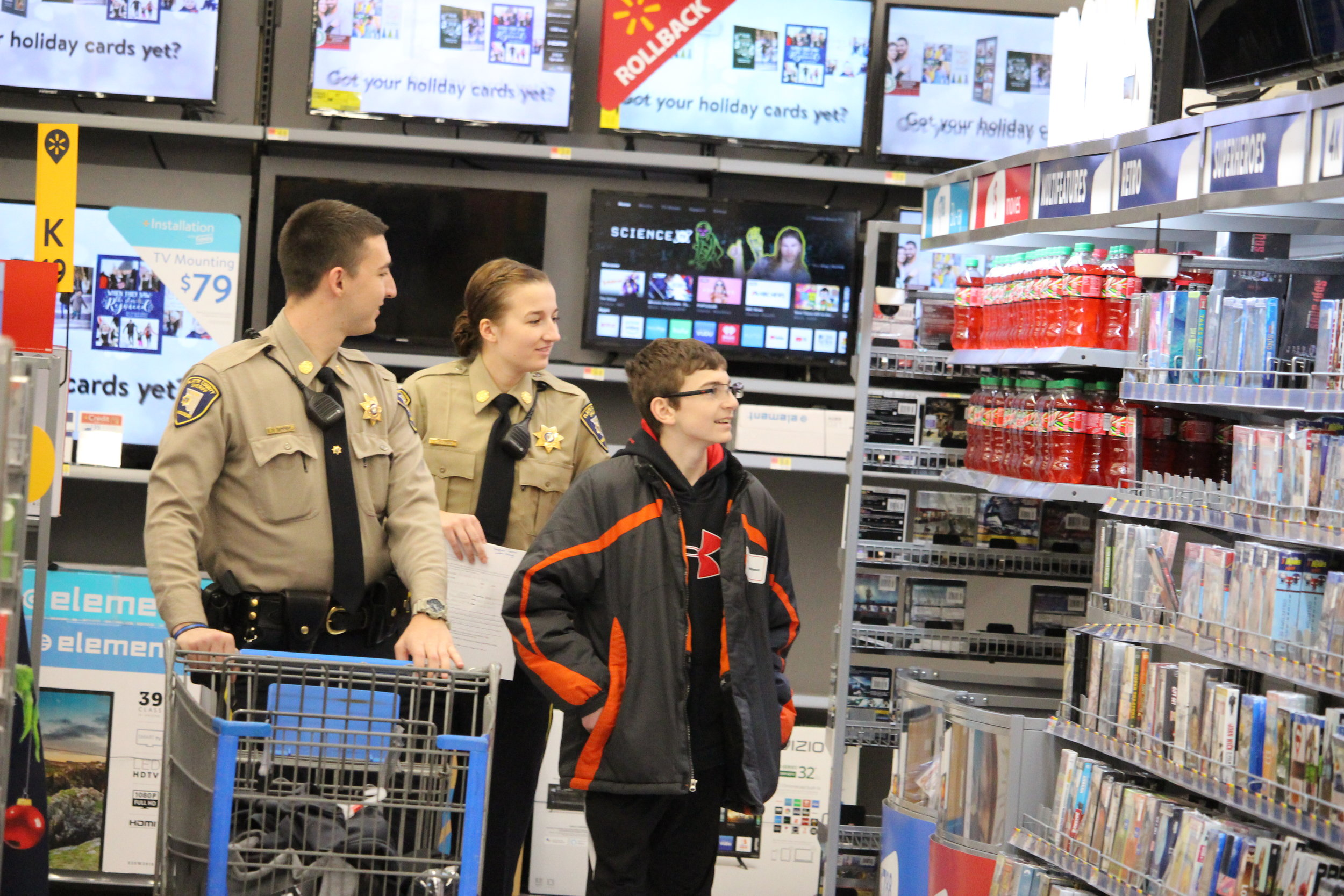 Thaddeus, far right, scopes out some movies at the Boardwalk Walmart on Saturday, Dec. 1 at the Shop With A Cop event in Kansas City North. Joining him are Platte County Sheriff's deputies Steven Tanner and Laken Kroge. CODY THORN|Citizen photo