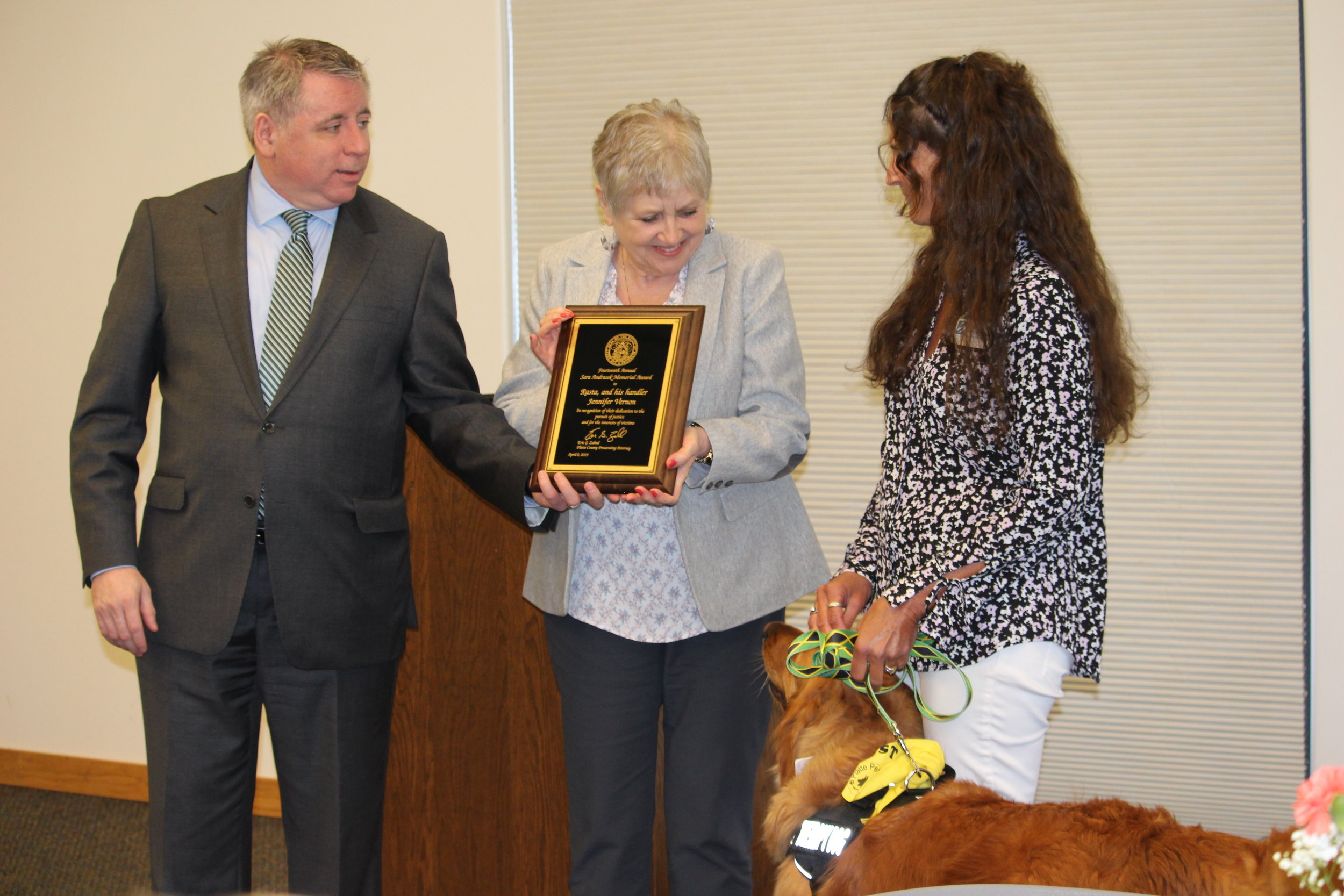 JEANETTE FAUBION/Citizen photo Platte County prosecutor Eric Zahnd and Sara Andrasek's mother, Janet Williams, presented the memorial award to Rasta and his owner Jennifer Vernon.