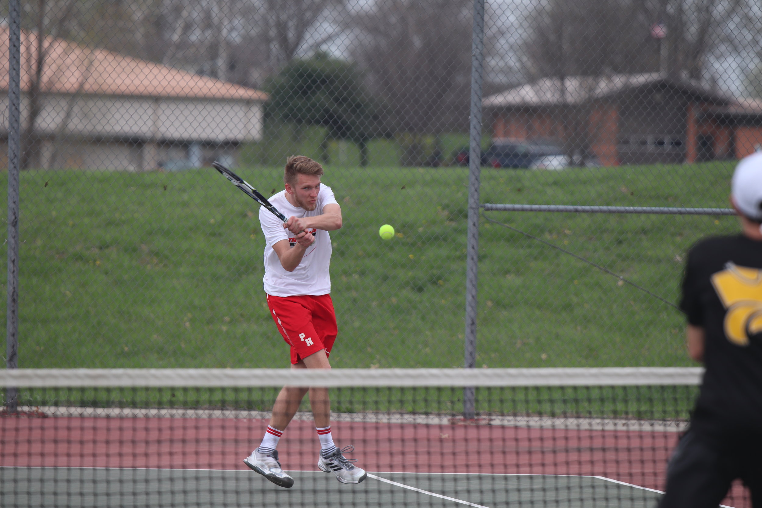 CODY THORN/Citizen photo  Park Hill's Evan Ericksen returns a shot in a match against Blue Springs on Wednesday, April 10 at the Park Hill Doubles Tournament at Barry Park in Kansas City. The Trojans finished fifth overall after beating Blue Springs.