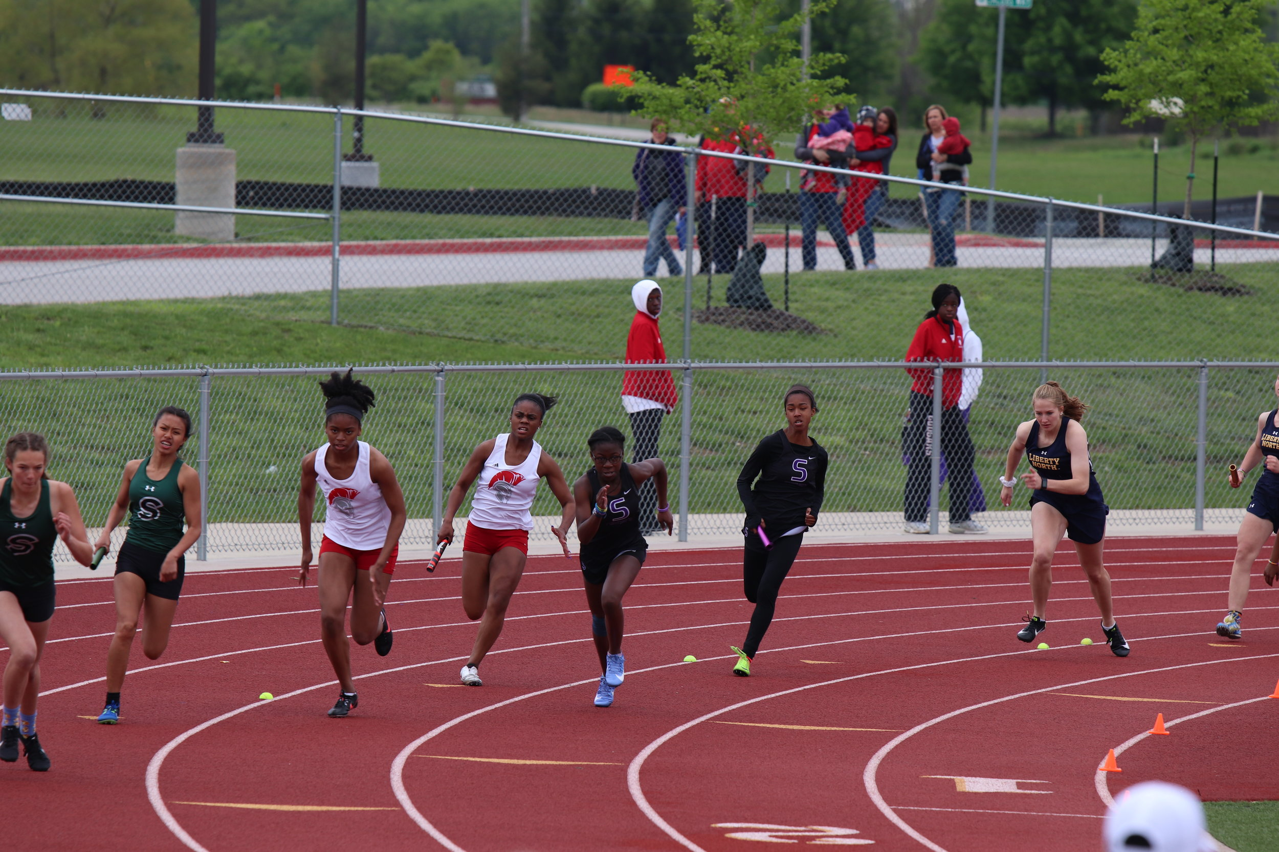 CODY THORN/Citizen photo Park Hill's Jordan Birmingham, third from right, gets ready to hand the baton to her sister, Kristen Birmingham, during the 4x100-meter relay at the Class 5 District 8 meet. Next to Park Hill is Park Hill South's Alex Hammonds, far right, as she prepares to get the baton to Nakiya Woodley.