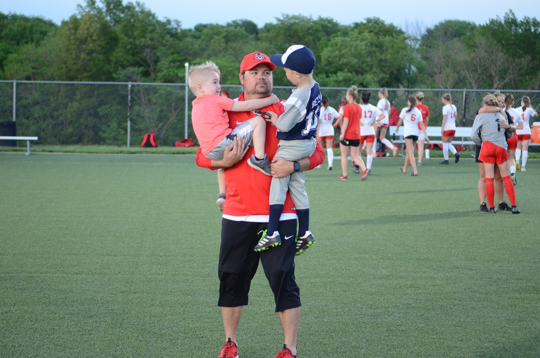 LEN LEHMANN/Special to the Citizen  Park Hill girls soccer coach Brandt Bell, center, holds his sons Holden, left, and Dash, right, at the conclusion of a game earlier this season. Bell resigned as the head coach of the girls program, where he led the team to the Class 4 title in 2018.