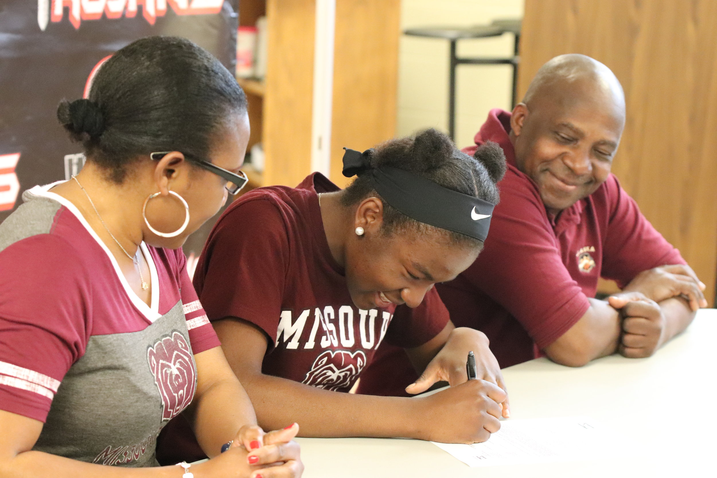 CODY THORN/Citizen photo  Park Hill's Manuel Ngo Tonye Nyemeck, center, signs a national letter of intent to compete at Missouri State. She is sitting between her parents Desire and Rosette Tonye Nyemeck