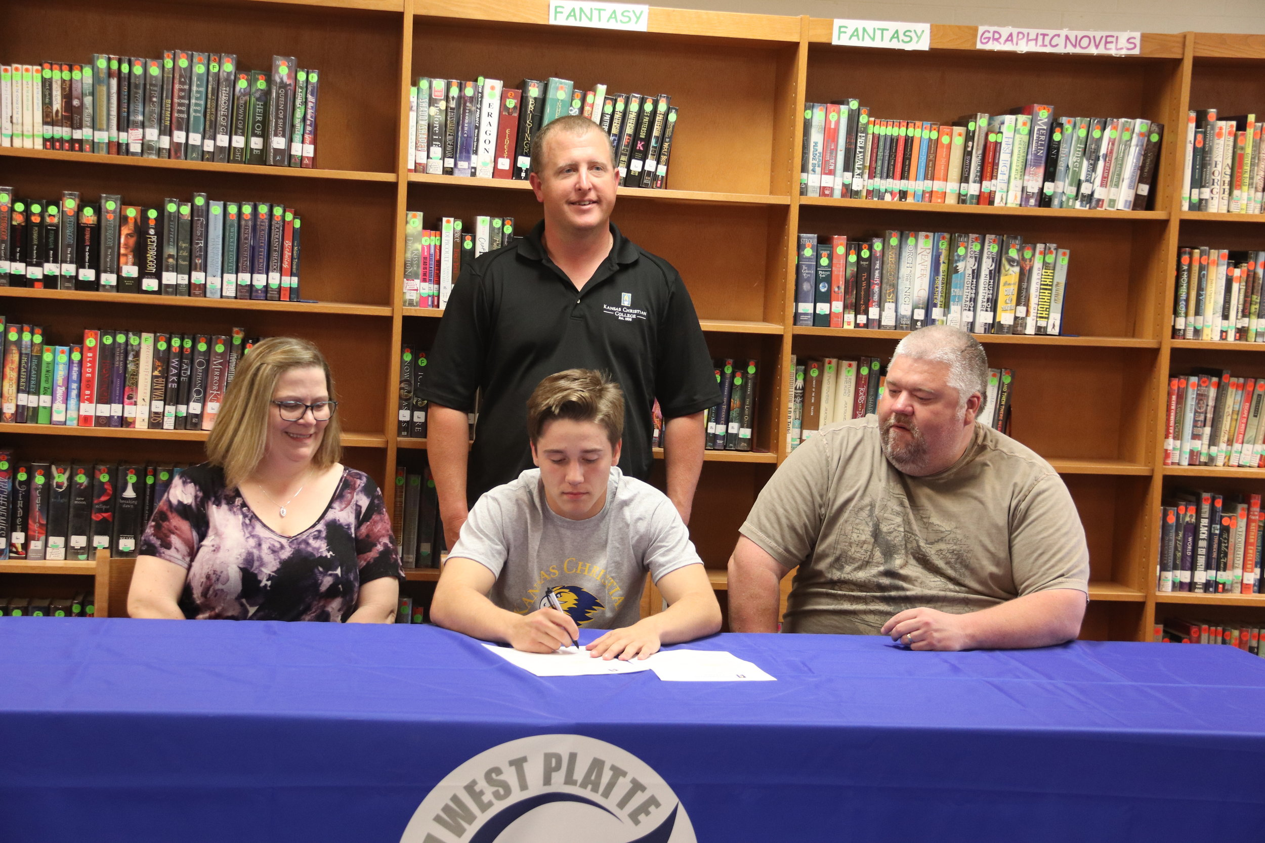 CODY THORN/Citizen photo  West Platte baseball player Gavin Davis, center, signs a letter of intent to compete at Kansas Christian College. Davis is flanked by his parents Carol and Aaron Davis, while KCC coach Tony Hurla stands in the back.