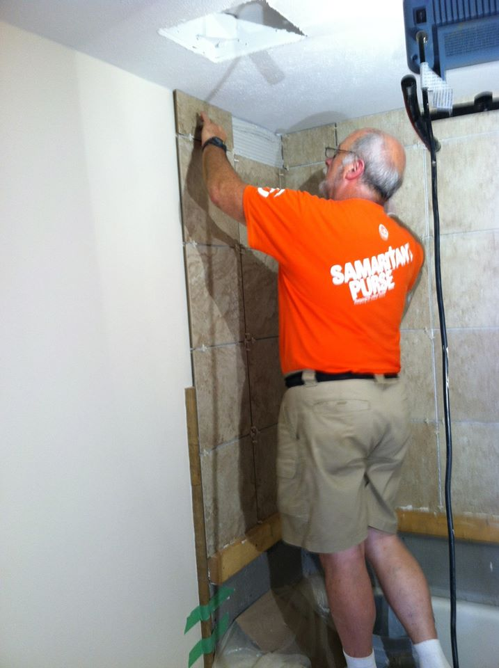 Bathroom tile being installed by Jim in the shower of the bathroom which is also a tornado safe room