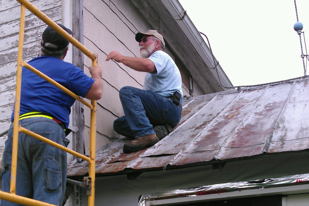 Ben and Jim try to figure out how to install the house wrap on the second story.