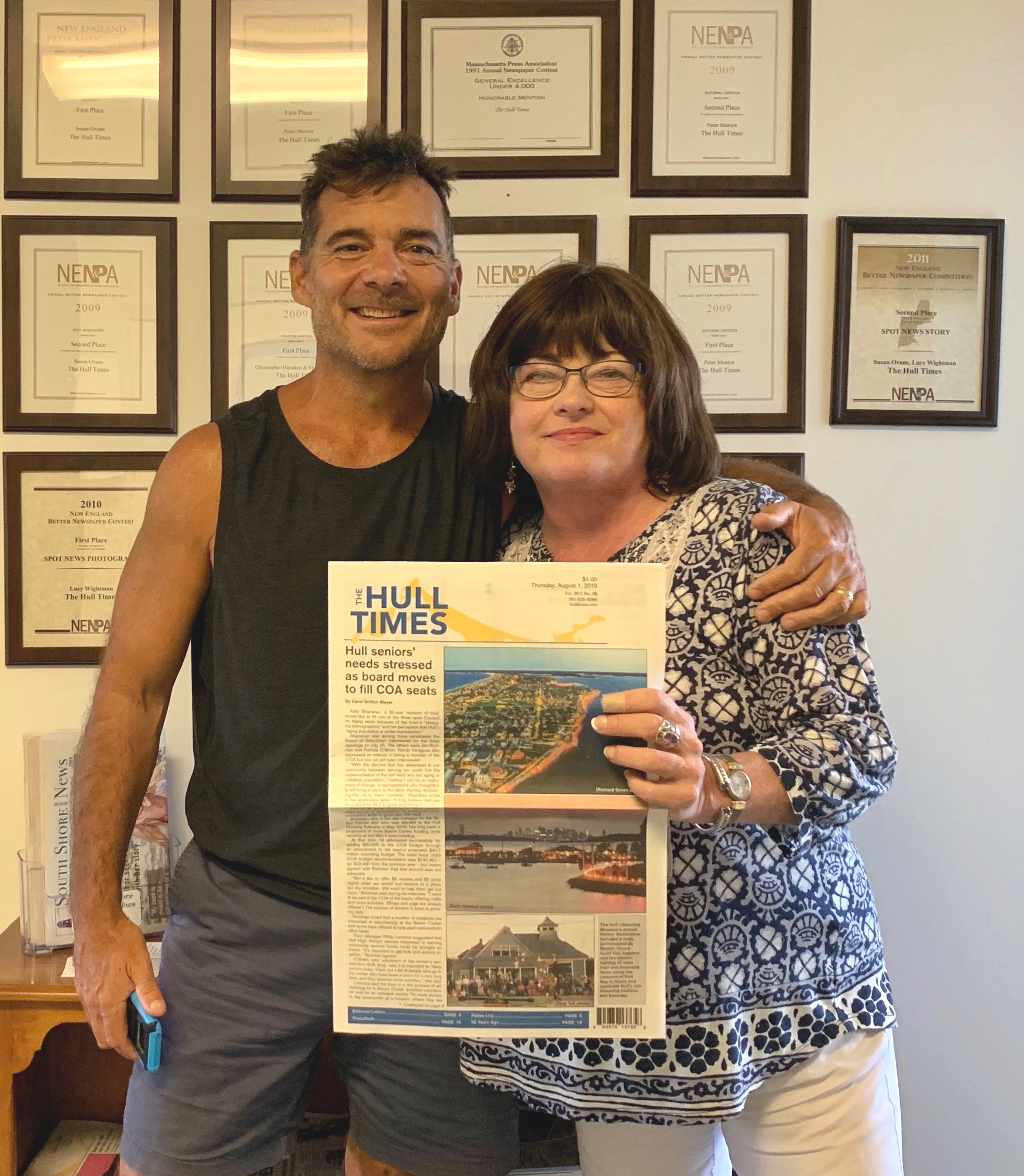 - The Hull Times' award-winning cartoonist, Peter Menice, with publisher Patricia Abbate at the publication's offices located on Nantasket Ave., Hull, MA.