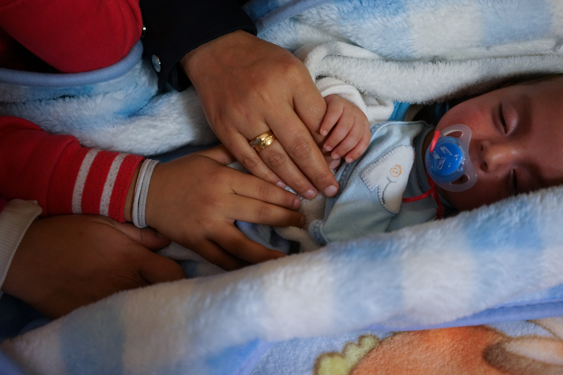 Iman and her daughters hold hands with her baby son at Faros Walk-in Center in Athens. Photo: Talitha Brauer