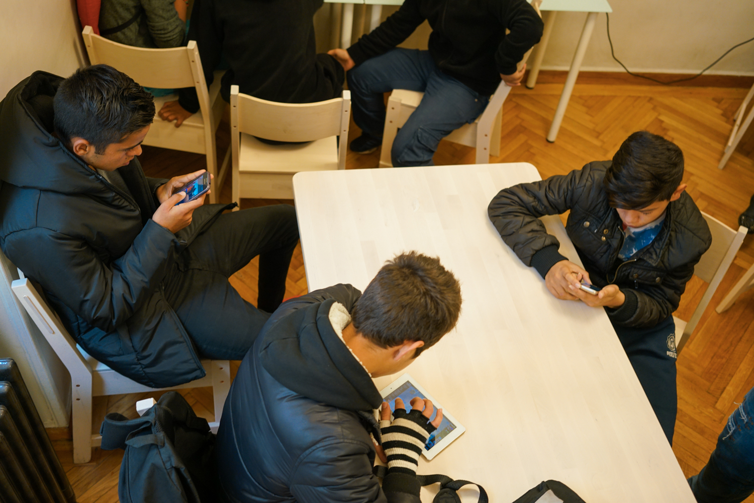 The boys play games on their phones in the dining room of Faros shelter for unaccompanied minors. Photo: Talitha Brauer