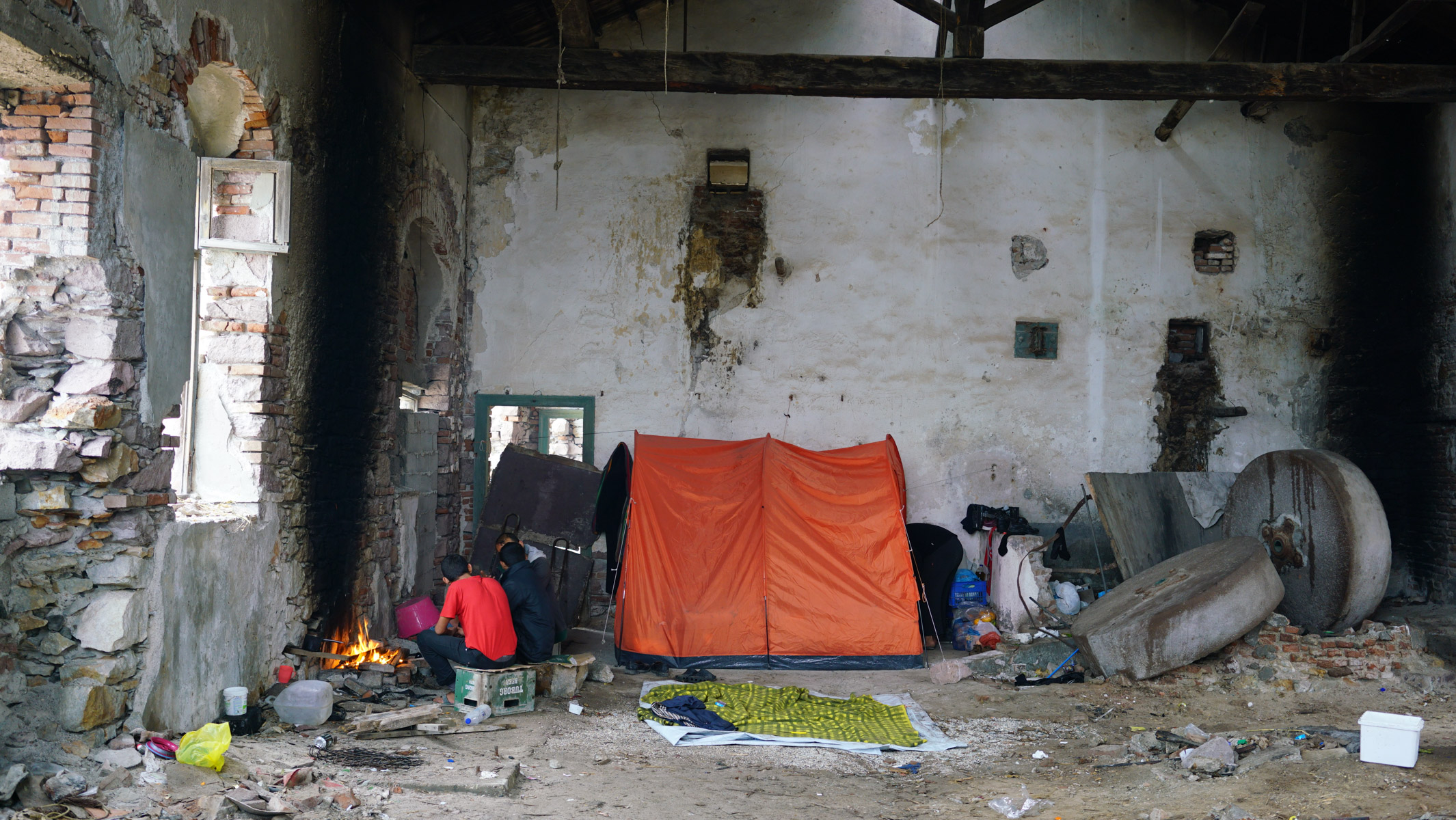 Syrian men make camp in an abandoned building. Panagiouda, Lesvos, Greece. November 2016. Photo: Talitha Brauer