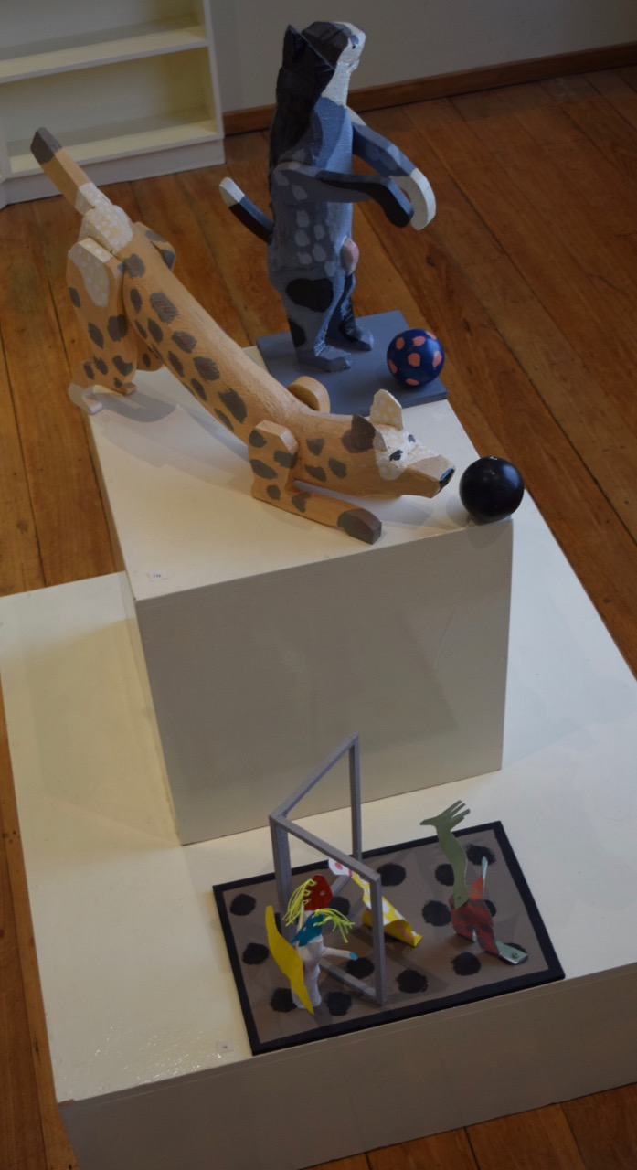 Installation:  playful dogs , painted wood, 2012;  Gabriel at the window , painted wood and metal, 2010