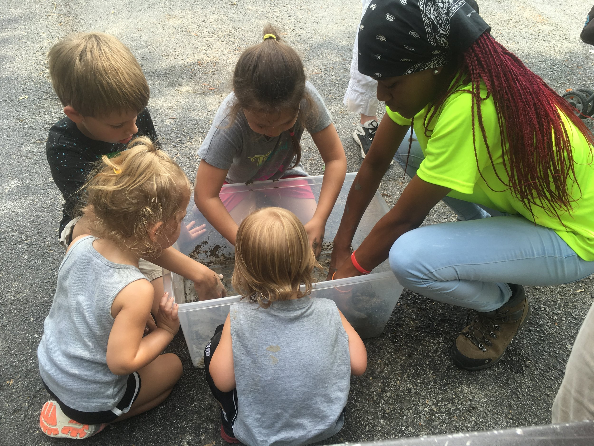 "Green Team Conservation Corps summer youth employee Keriyanna teaches children how to make seed balls at a Dallas Zoo ""Save the Monarchs"" event."