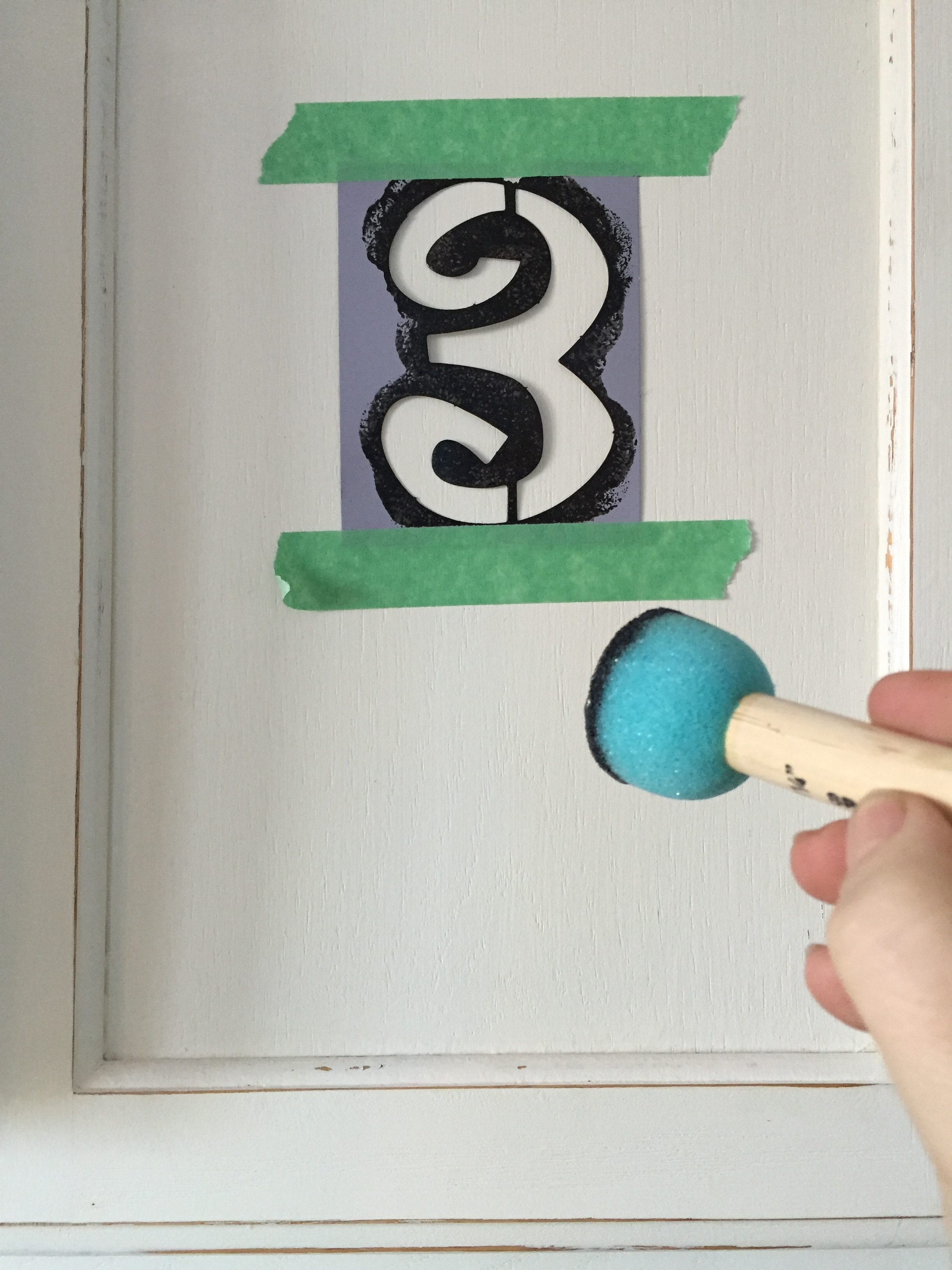 adding paint with a stencil and sponge applicator