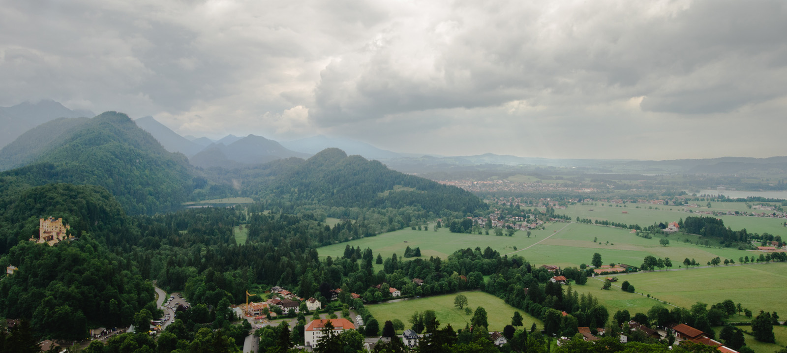 A stormy day in the Alpine foothills in western Bavaria. This view, from a balcony of the Schlöss Neuschwanstein, features the nearby Schloss Hohenschwangau at the edge of the mountains.