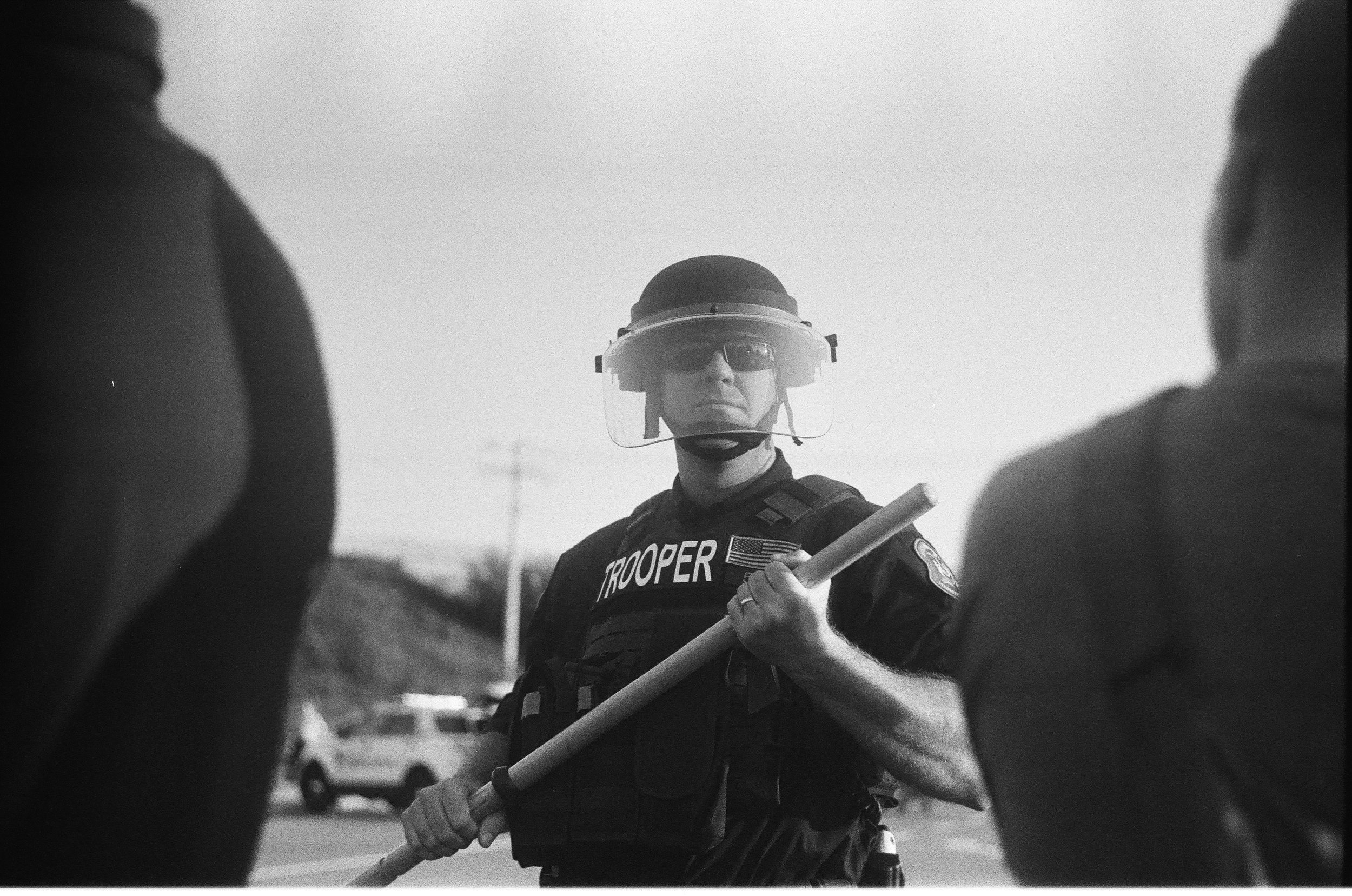 A police officer in protective gear holds a club in St. Louis.