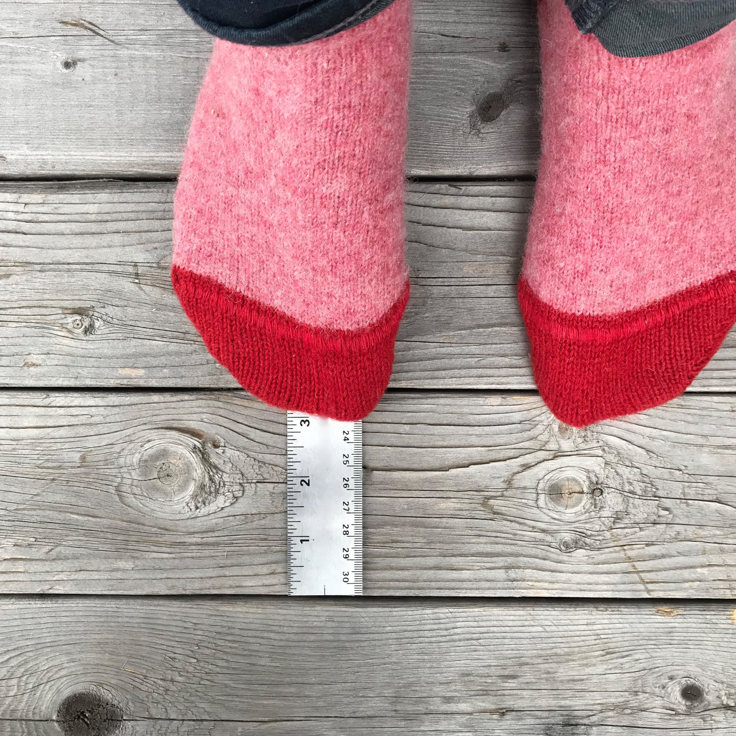 Stand on top with your heel against the wall and the longest part of you foot over the millimetre measurement. Record this measurement. (In this photo, the measurement is 231mm)