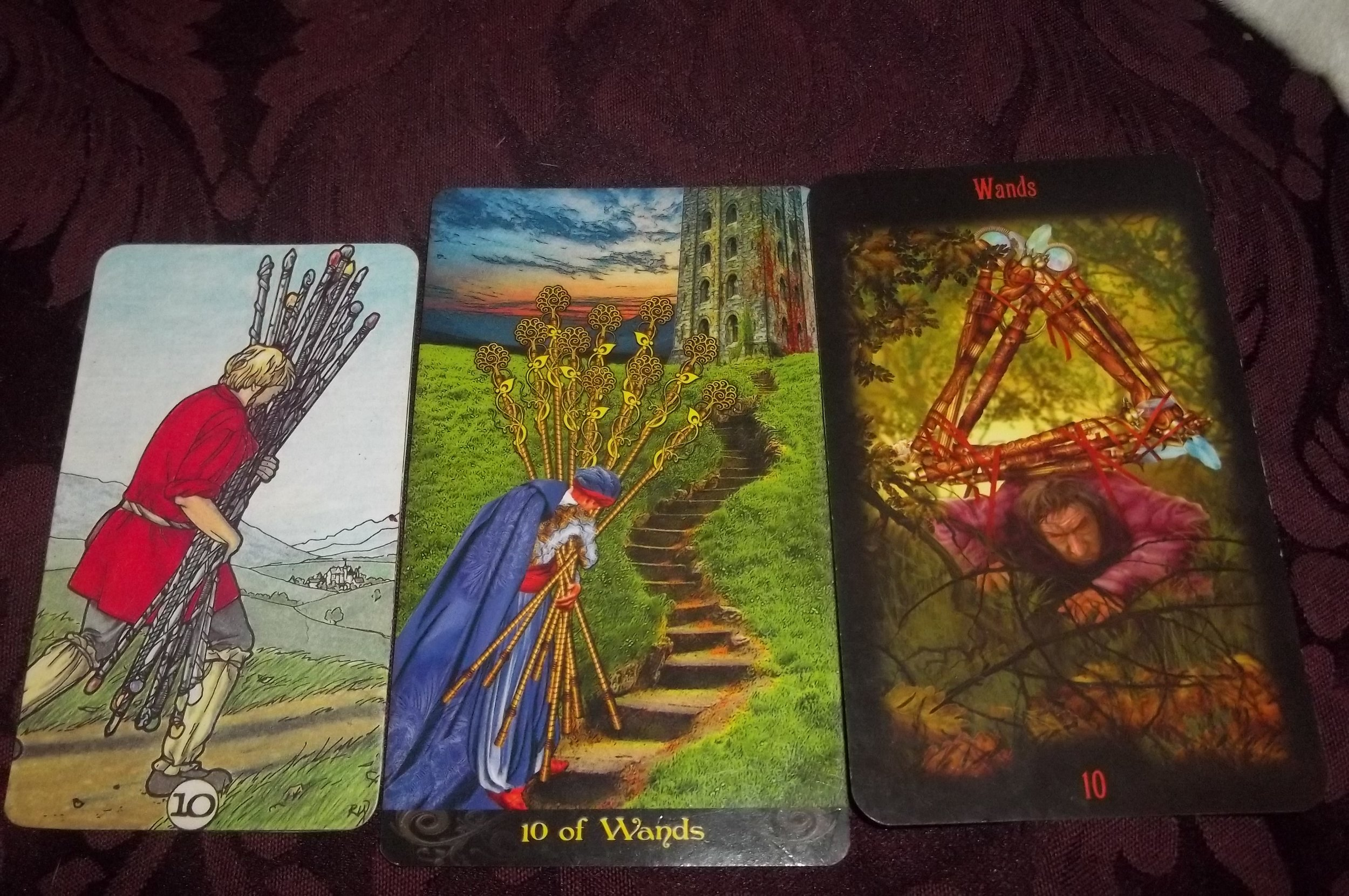 Ten of Wands depicted in the Robin Wood Tarot, Tarot Illuminati, and Tarot of Divine Legacy