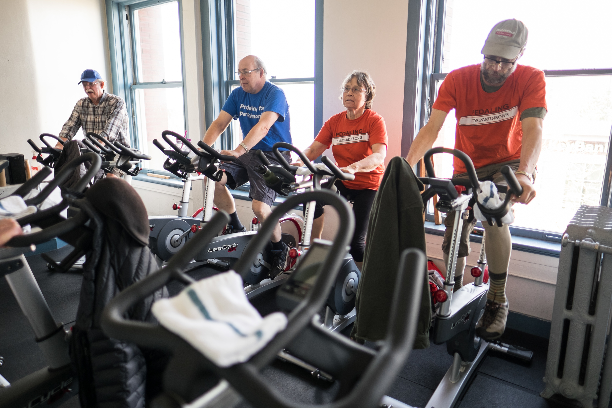 RICK HERMANN (RIGHT) PEDALS AWAY DURING HIS YMCA SPIN CLASS THAT HELPS HIM COMBAT THE SYMPTOMS OF PARKINSON'S DISEASE. CLASS MEMBERS SPEND THE HOUR TALKING OR LISTENING TO MUSIC. For Klipsun Magazine