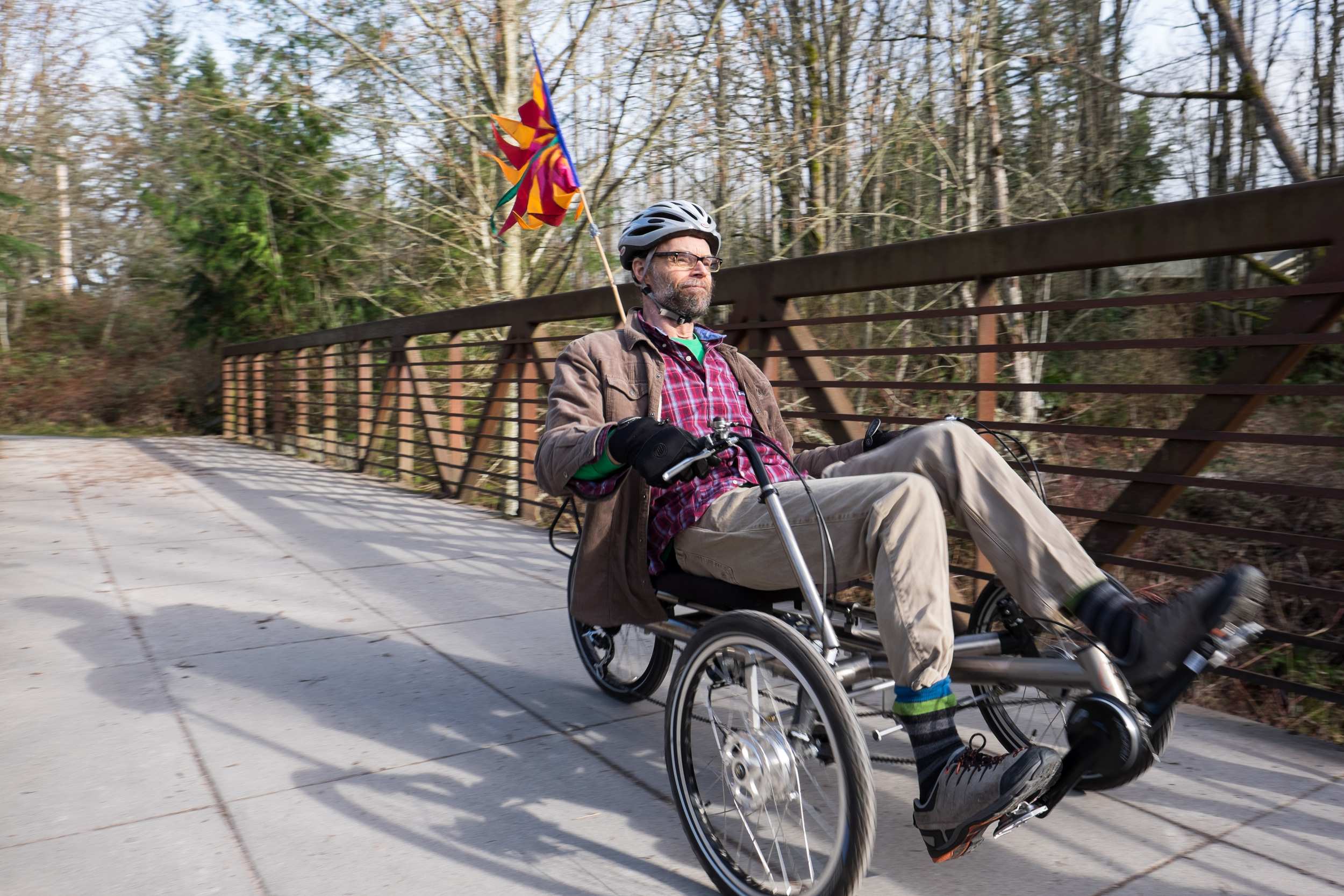 HERMANN ON HIS RECUMBENT BIKE ON BELLINGHAM'S RAILROAD TRAIL NEAR WHATCOM FALLS PARK. A RECUMBENT BIKE HAS HELPED HERMANN GET OUTSIDE TO STAY ACTIVE AND HAS ALSO SERVED AS AN ALTERNATE MODE OF TRANSPORTATION. For Klipsun Magazine