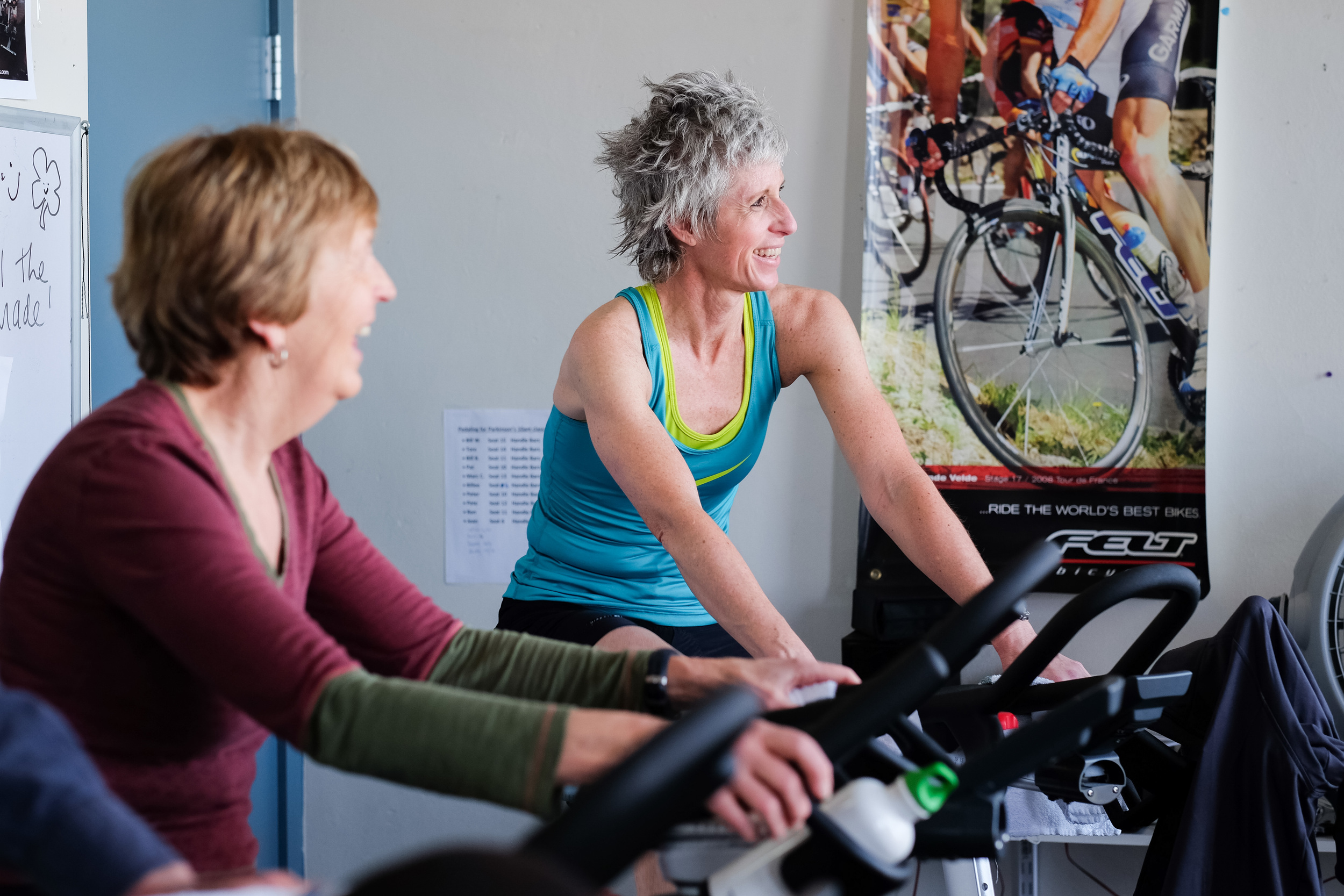 TRACY DHIEL, AN INSTRUCTOR AND LEADER OF THE PEDALING FOR PARKINSON'S CLASS AT THE YMCA, CHATS WITH PARTICIPANTS DURING THE HOUR BIKE RIDE. STUDIES HAVE SHOWN THAT SPIN CLASSES LIKE THIS ONE CAN HELP REDUCE SYMPTOMS FOR PARKINSON'S BY AROUND 35 PERCENT, ACCORDING TO THE YMCA. For Klipsun Magazine