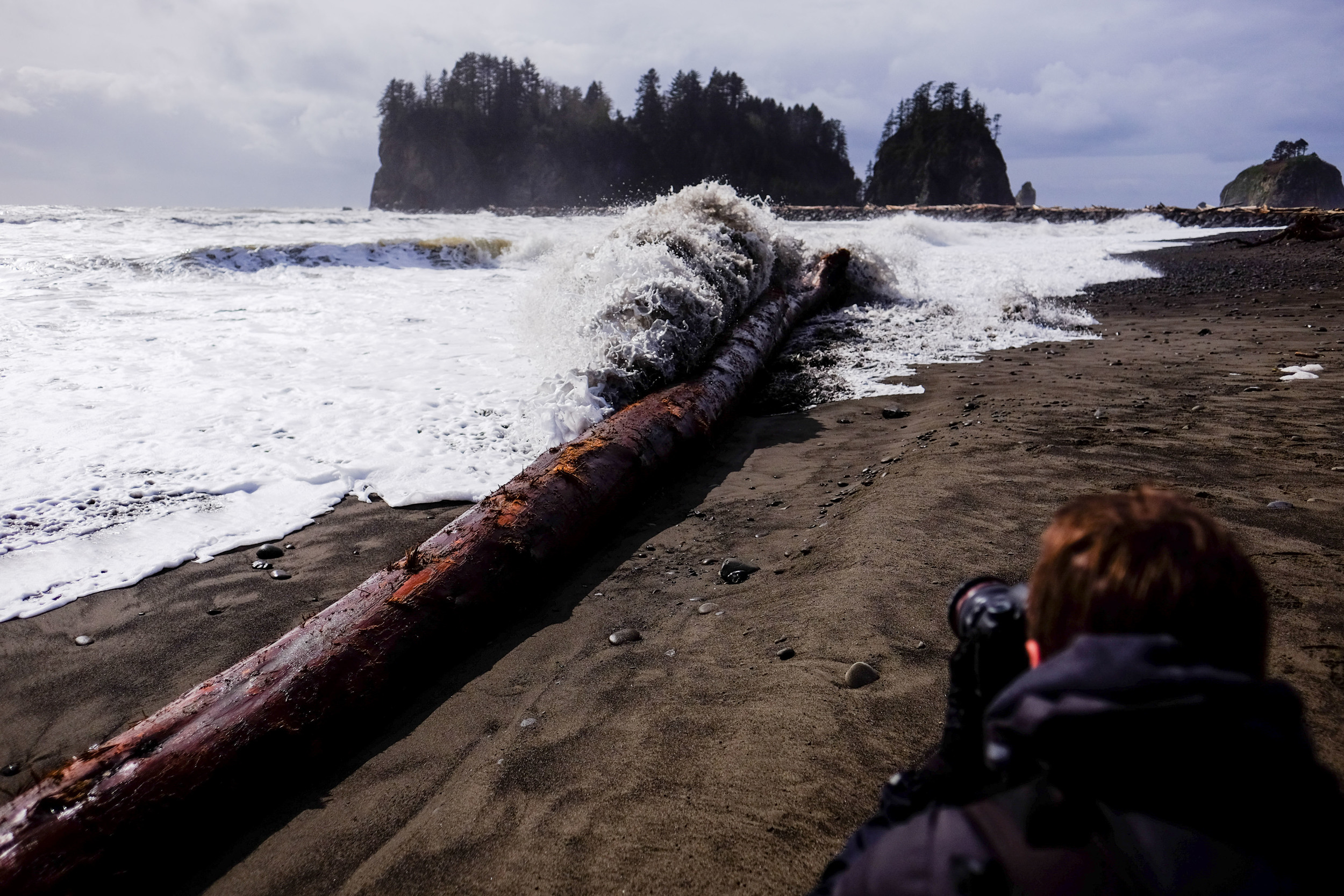When two photographers try to get shots of a wave hit a log... and then having to run back to avoid getting soaked.