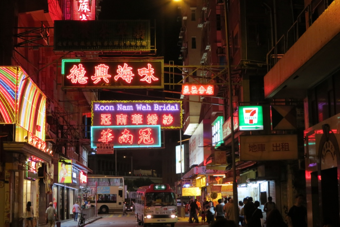 Neon lights beckon night owls to the Temple Street Night Market in Hong Kong