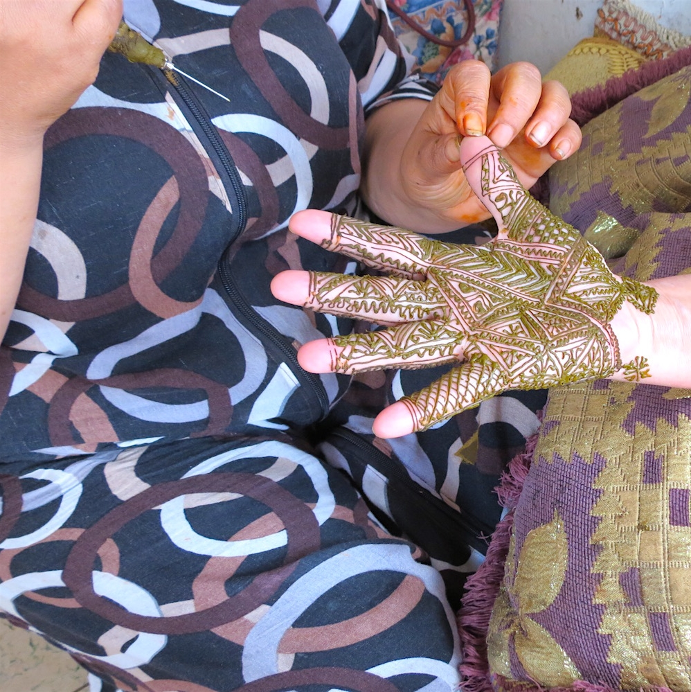 Street vendors apply henna to hands and feet in Casablanca's Habous Quarter