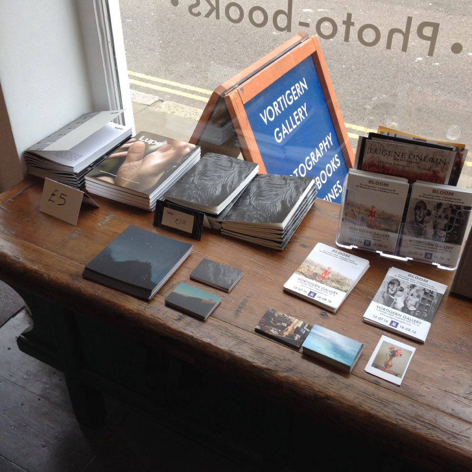 <^ The selection of books and postcards available at the gallery.