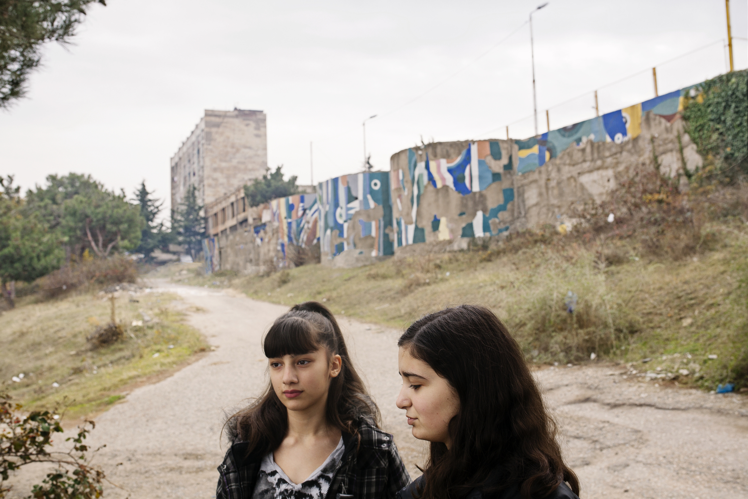 From the series  Land of Wolves   Megi & Ana two young Abkhazian IDP'€™s (Internally Displaced People) stand outside the ex soviet hotel they call home, both where born in Tbilisi and though neither has been to Abkhazia they count themselves as displaced. Despite living in the hotel their whole lives the Georgian government still considers the accommodation temporary.