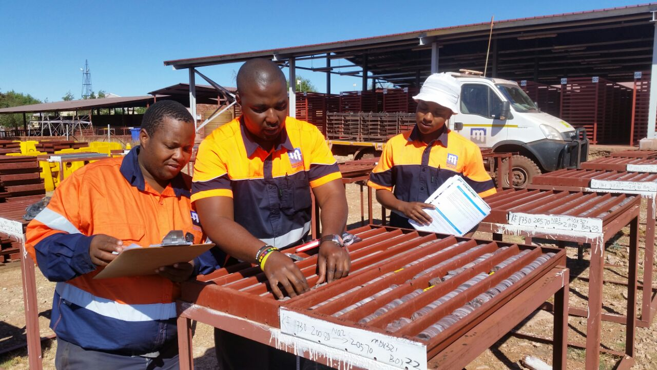 Trained Master Drilling scribes check the quality of core with Master Drilling geologist Mlamleli Chopela.