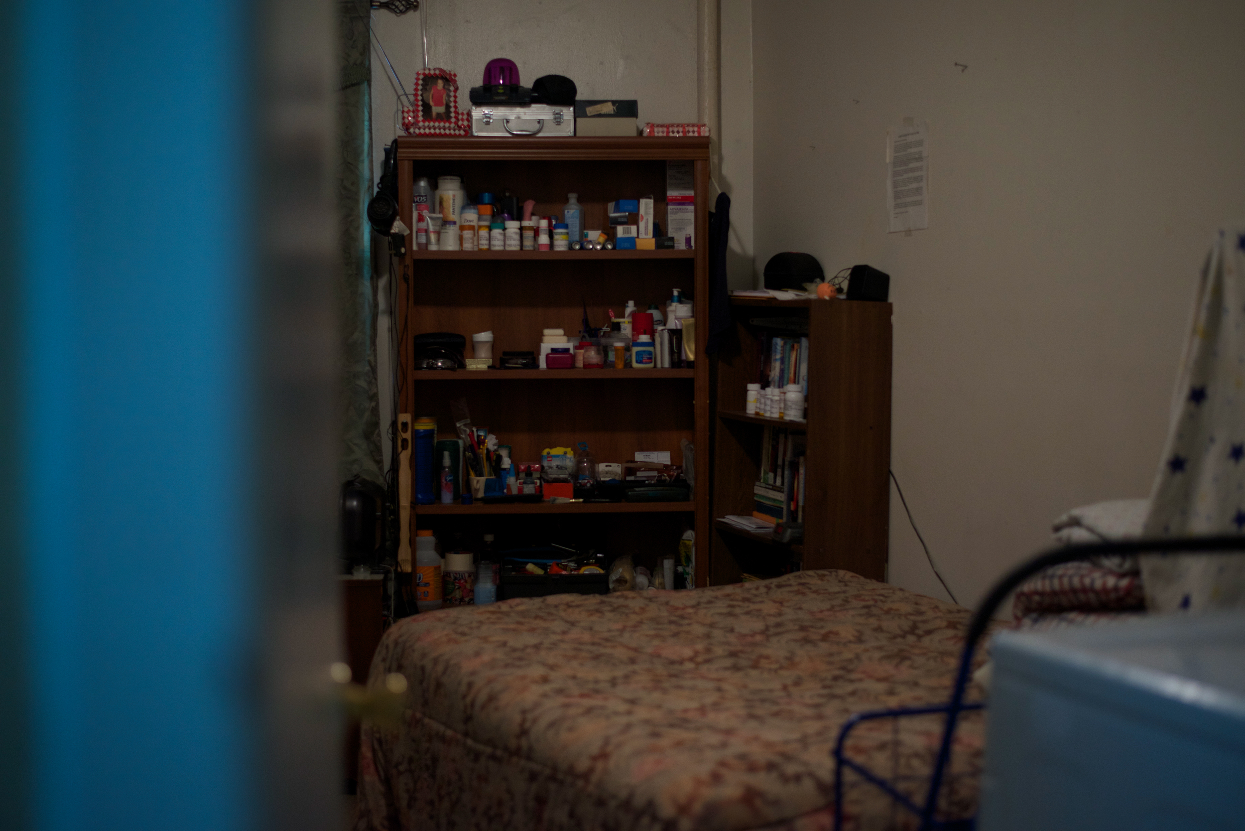 Medication, books and other personal belongings sit on bookshelves in Denis Reyes' bedroom. Reyes' brother, Wilfredo Bracero, said Reyes moved into his mother's apartment after he came out of jail.