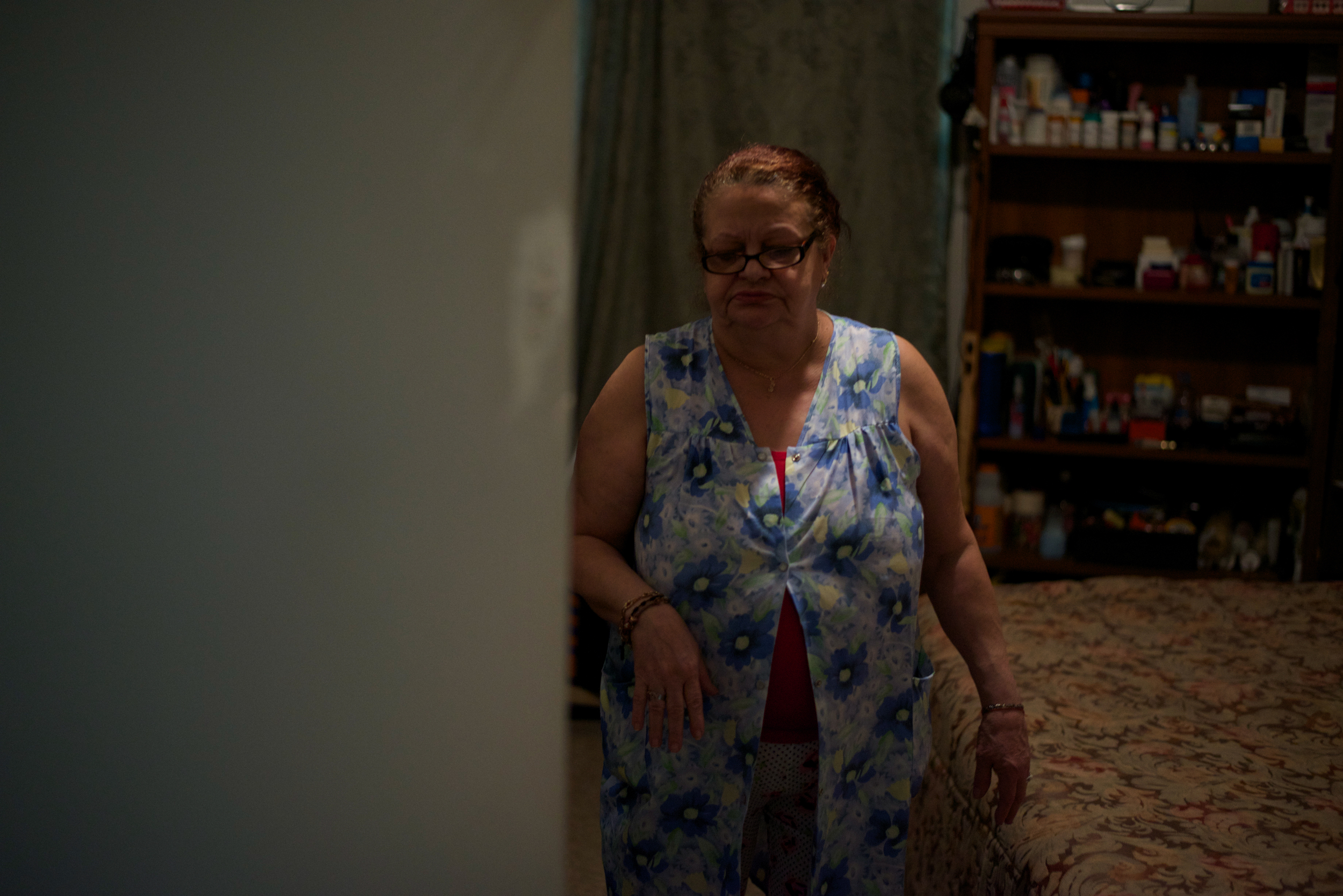 Blanca Sierra, the mother of Denis Reyes, leaves her son's bedroom after looking through some of her son's belongings.