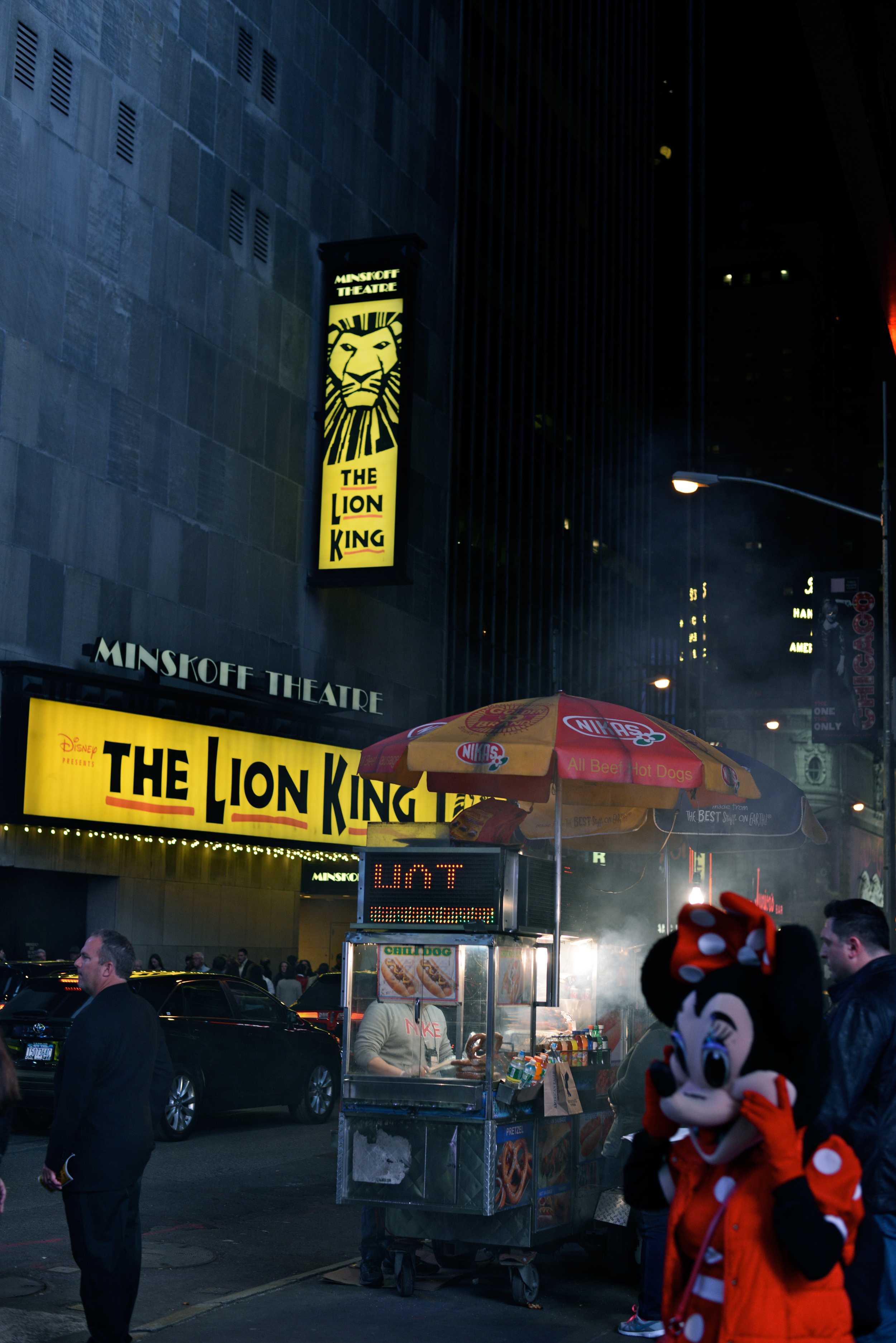A costumed worker dressed as Minnie Mouse walks by a food stand in Times Square, New York, on April 21, 2015.