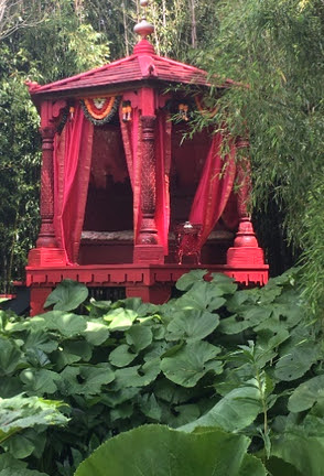 Not a wall but a room within a room, the Red Mughal Pavilion floats above a carpet of petasites.