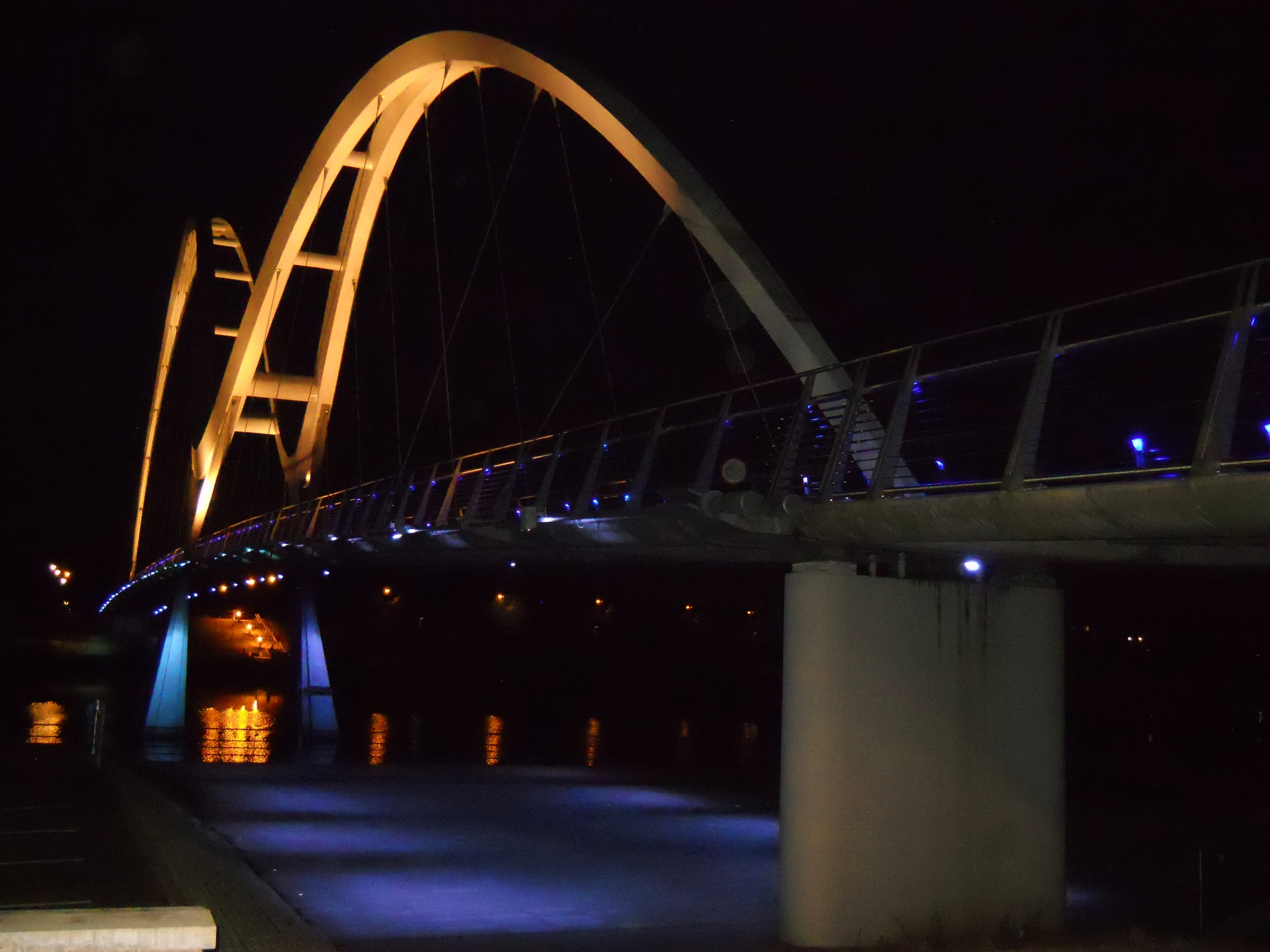 LED lighting changes from blue to white as pedestrians cross the bridge at night - Stockton's human 'comets'