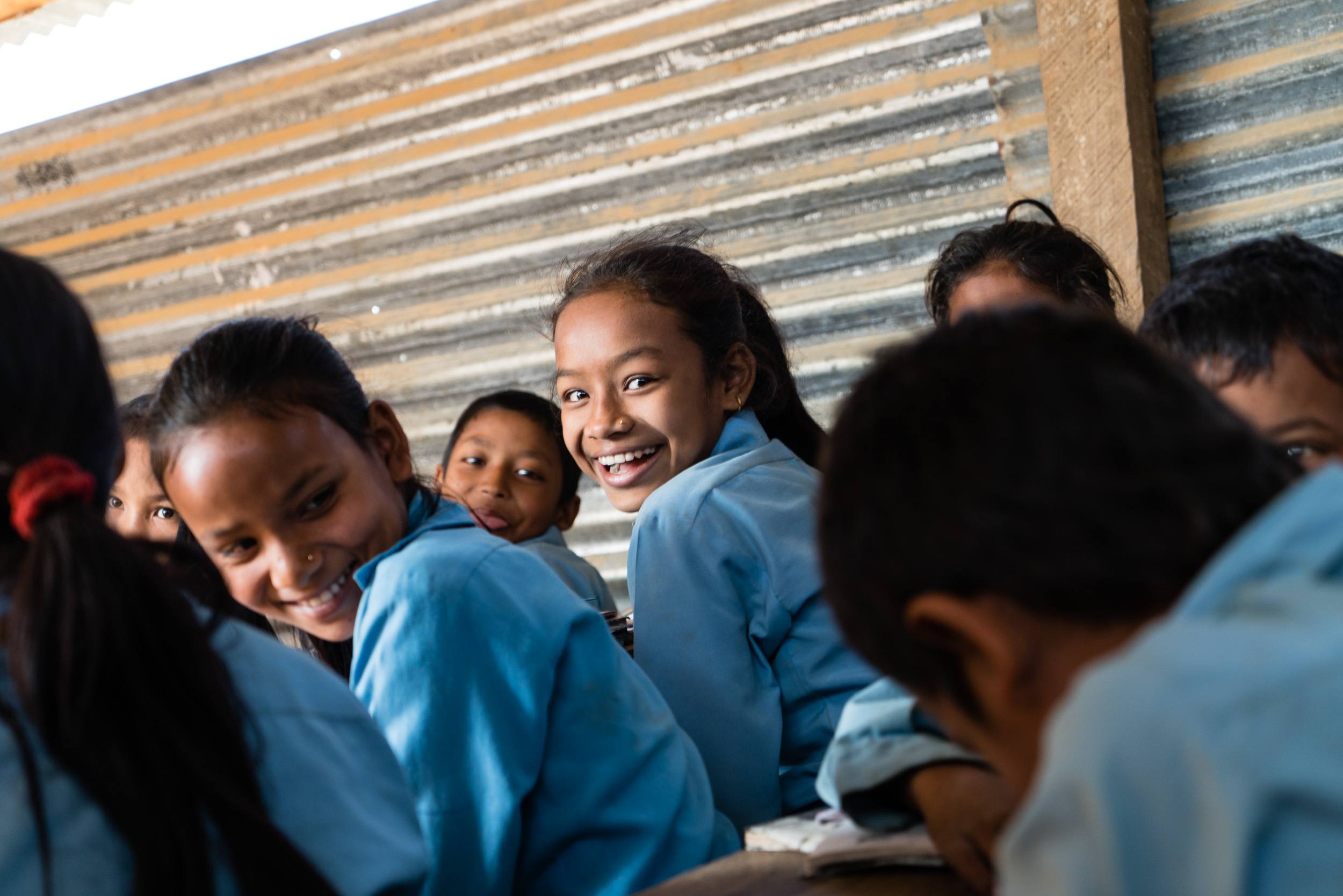 Even under difficult conditions in the temporary school these students are happy to have a place to learn.