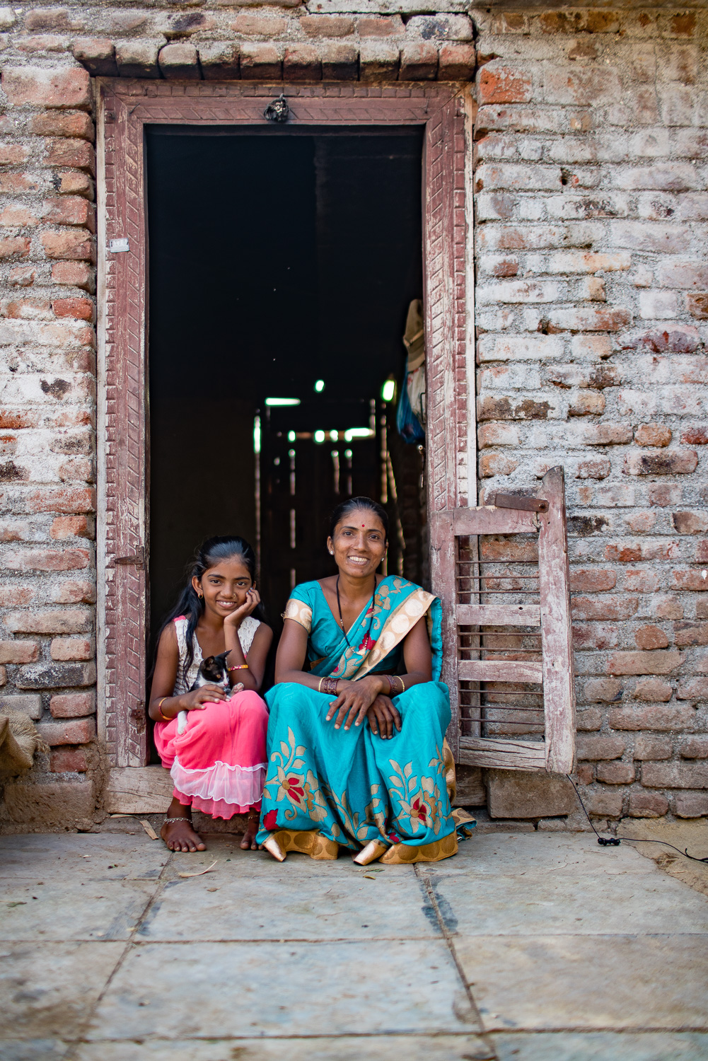 Mother and daughter at the doorway of their modest house.