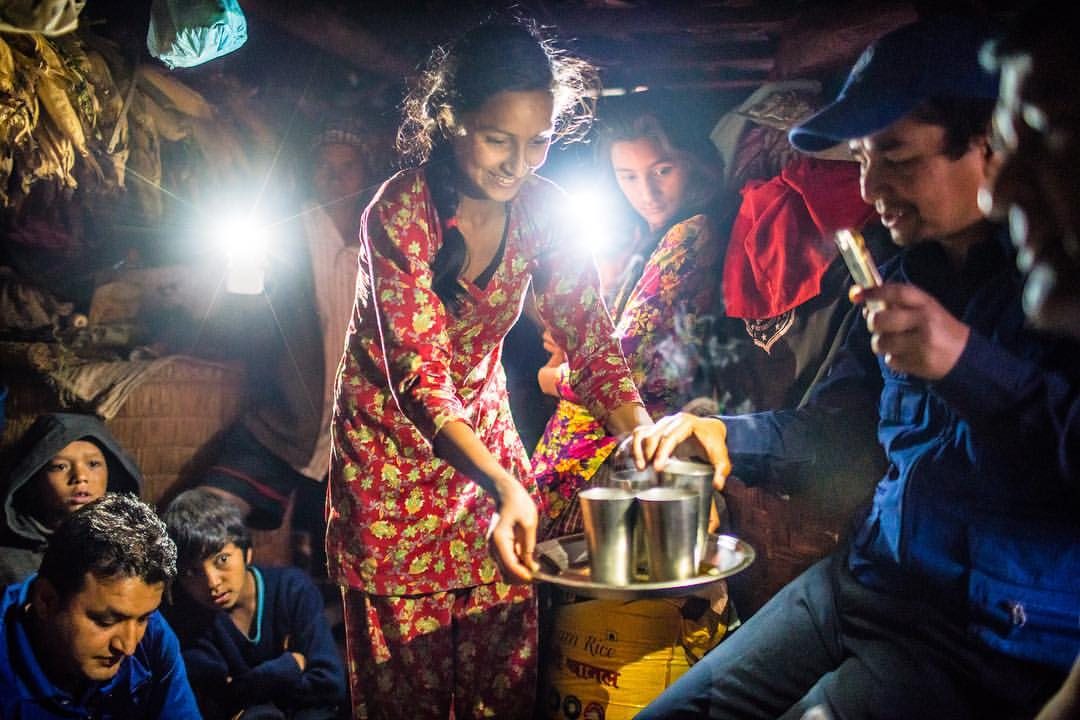 "One of my favorite images from 2016. It was from an assignment for @Americares. We crowded into Junkiri's tiny one room home in the mountains of Sindhupalchok to escape the pouring rain. It was literally pitch black inside, so dark that I didn't notice that right next to me there was ""grandfather"" who put his hand on my arm to guide me to a seat. I suspect that Nepalis can see in the dark. As I was having a conversation in the darkness. I contemplated how I was going to be able to photograph. Then someone turned the light on their phone, then another, and another. It was beautiful, and a solution to my dilemma. Jinkiri's daughter went around offering us, and what looked like half the village crammed into her hut some tea and freshly made popcorn made from the corn she had drying in her home. It was a beautiful moment, and after some arranging of the ""lights"" I was able to get a good representation of that moment. We should have stayed over that night. The drive back down the mountain was a nightmare of roads blocked by parts of homes and power lines brought down by the storm."