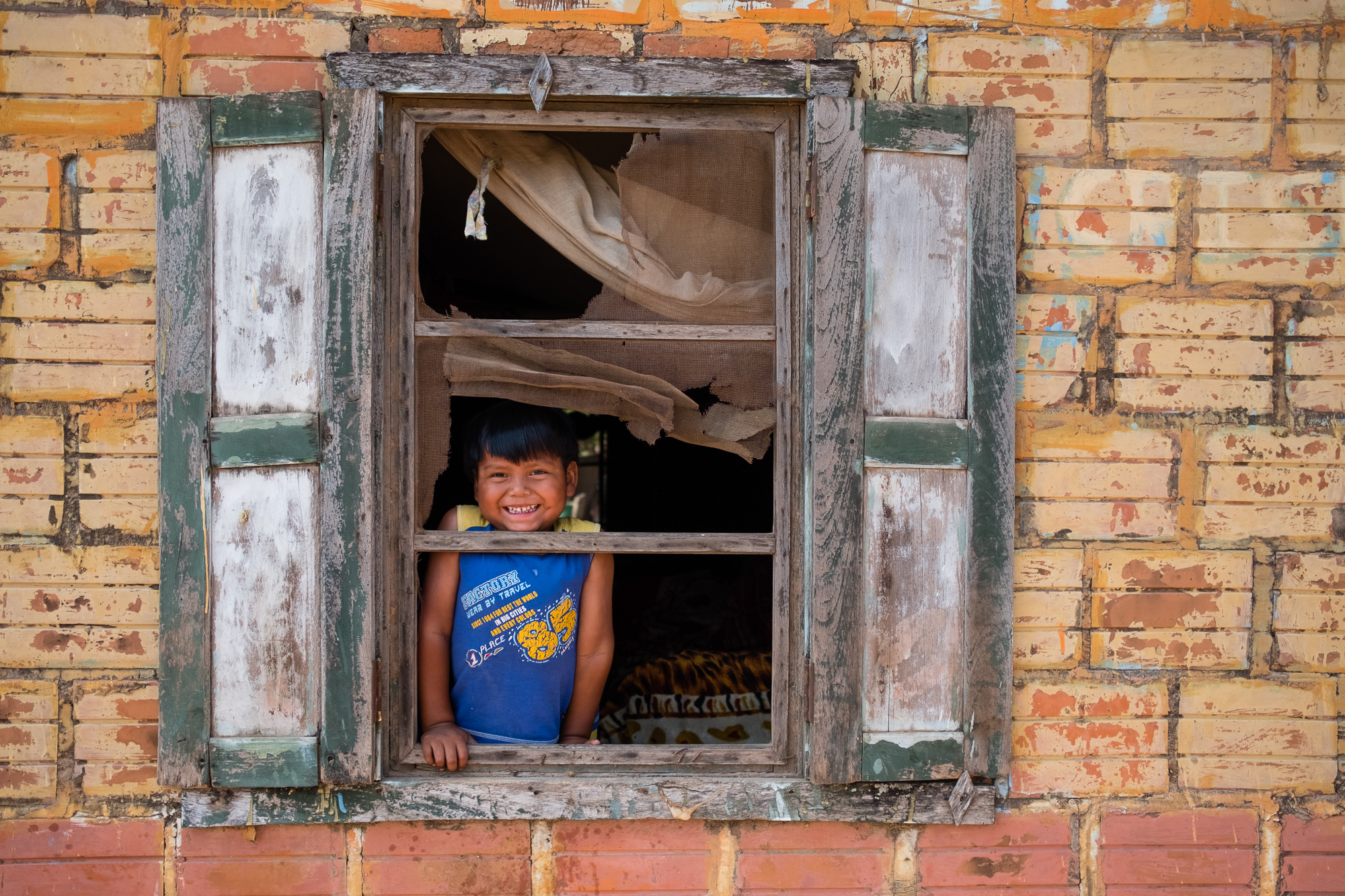 A little boy in the window of his home. El Chaco, Paraguay.