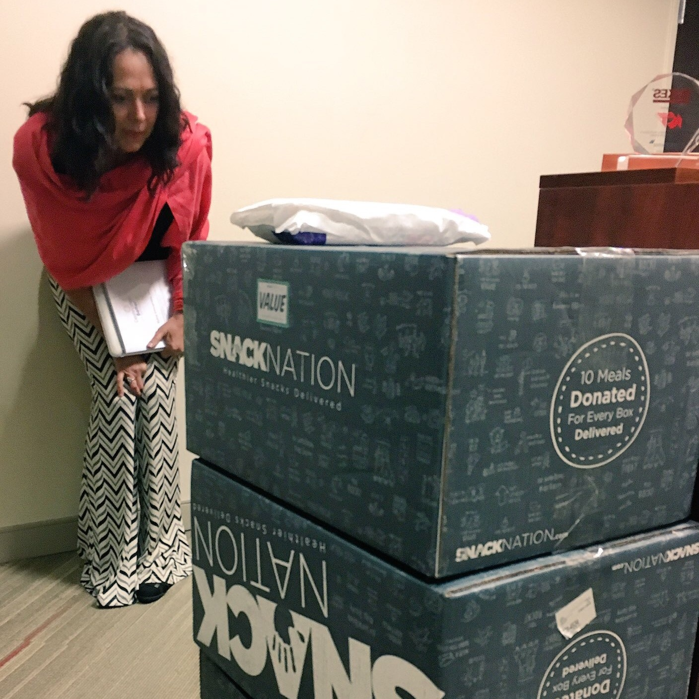Destination Better's janet craig checking out a  SnackNation  delivery, who donates 10 meals for every box delivered, in a company headquarters, Tampa Florida