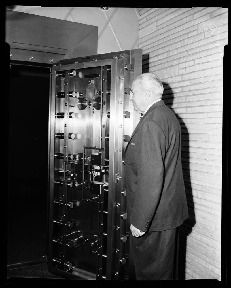 The picture shows Paul A. Palmer, former president of Newport Balboa Savings and Loan, demonstrating the vault within the building. Source:  USC Digital Library