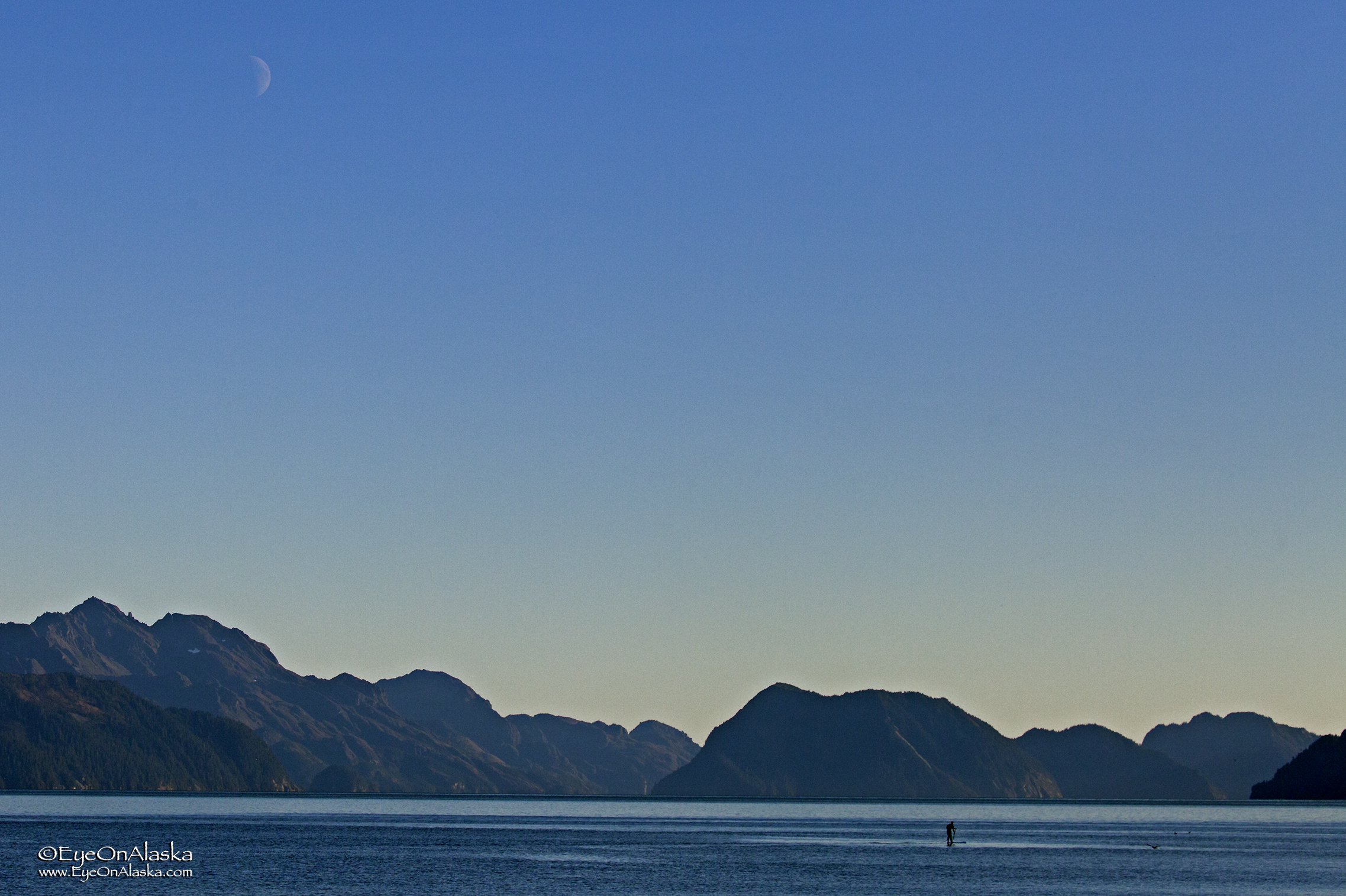 Paddle-boarding under a rising moon on an absolutely still evening.