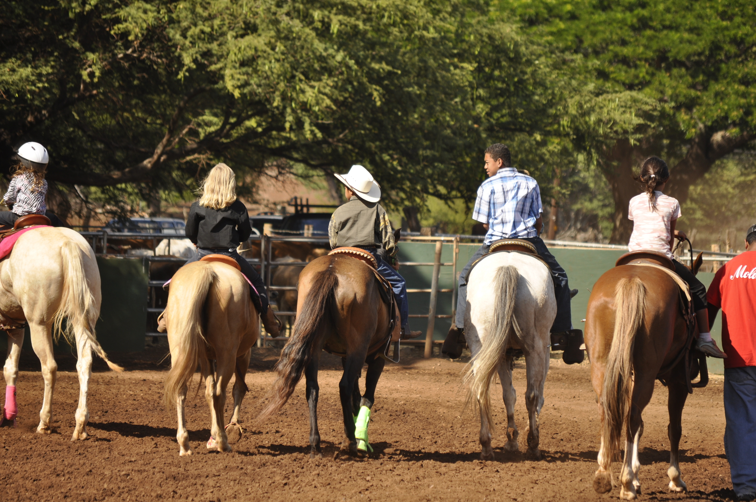 Young riders legging up their horses for barrel racing.