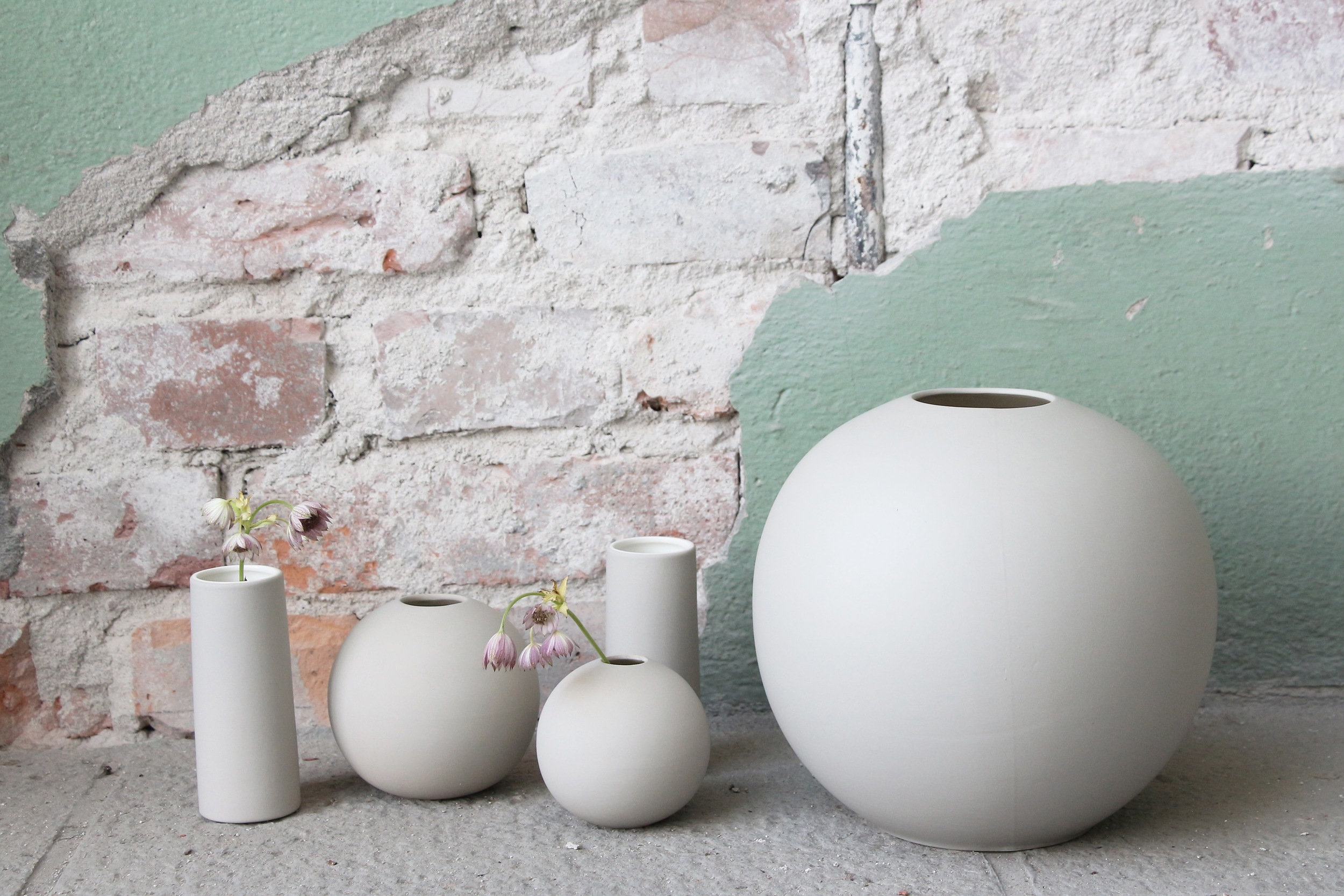 Ball vases and tube vases in sand.