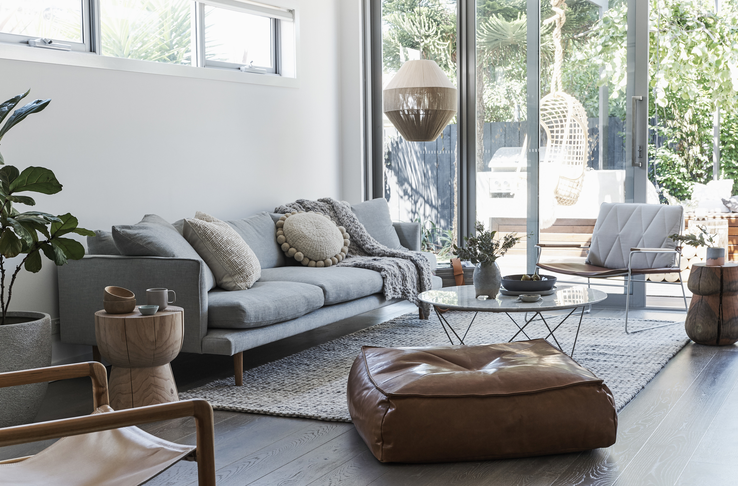 Natural timber is the hero in this warm, texural living space. Freddy Sofa  Huset , Seb chair, Stanley stool and Alby ottoman  Jardan , Egg cup stool  Mark Tuckey , Como marble coffee table  Globe West , Floor rug  Halcyon Lake , Smith leather sling chair  Barnaby Lane  and ceramics by  Bridget Bodneham  and  Marmouset Found . Dream weaver pendant light  Pop and Scott , cushions  We Are Pampa  along with flame throw also by  Tribe and Co .