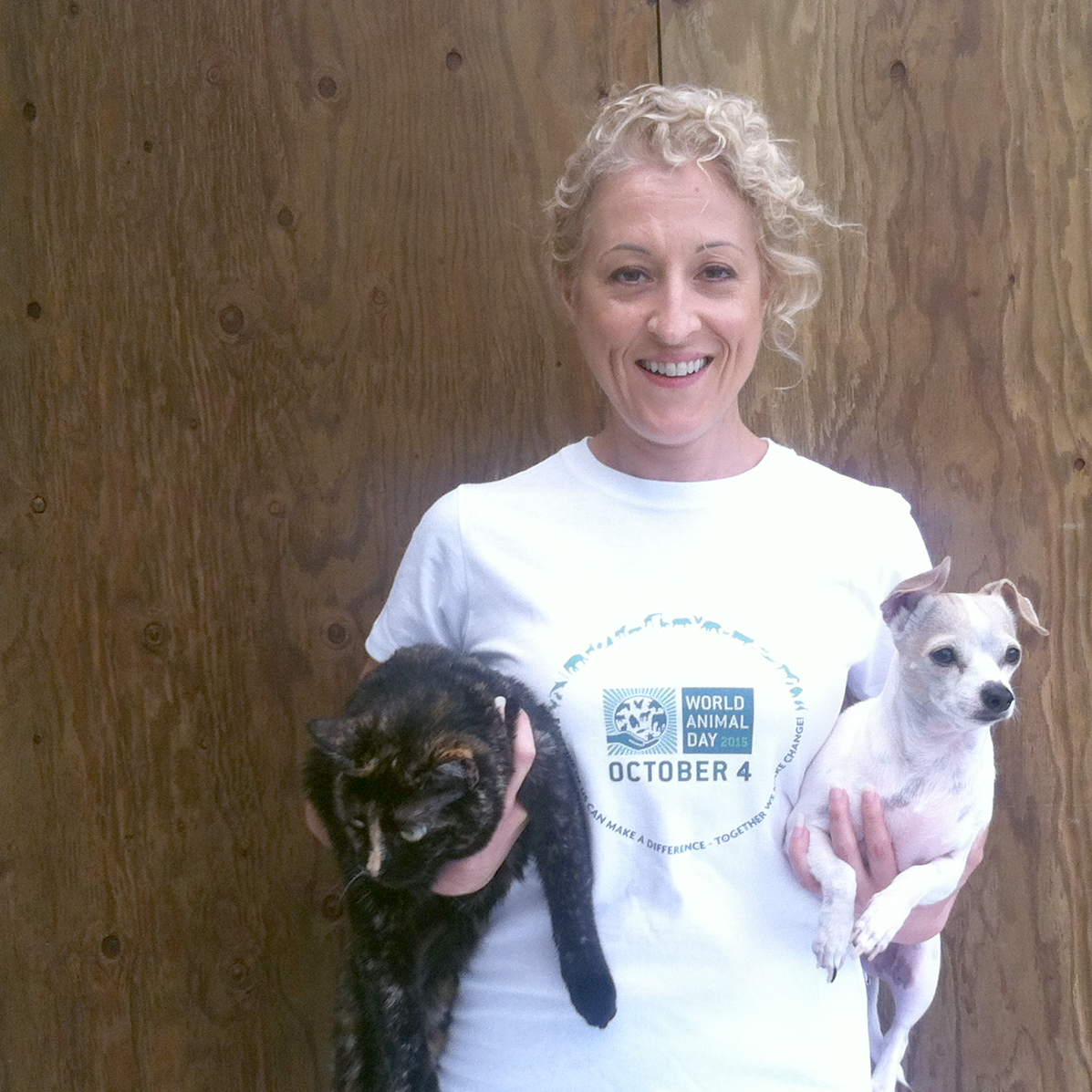 Wearing a shirt she designed for World Animal Day, this is Delia Bonfilio holding her cat, Xena, and dog, Dalai Mama.