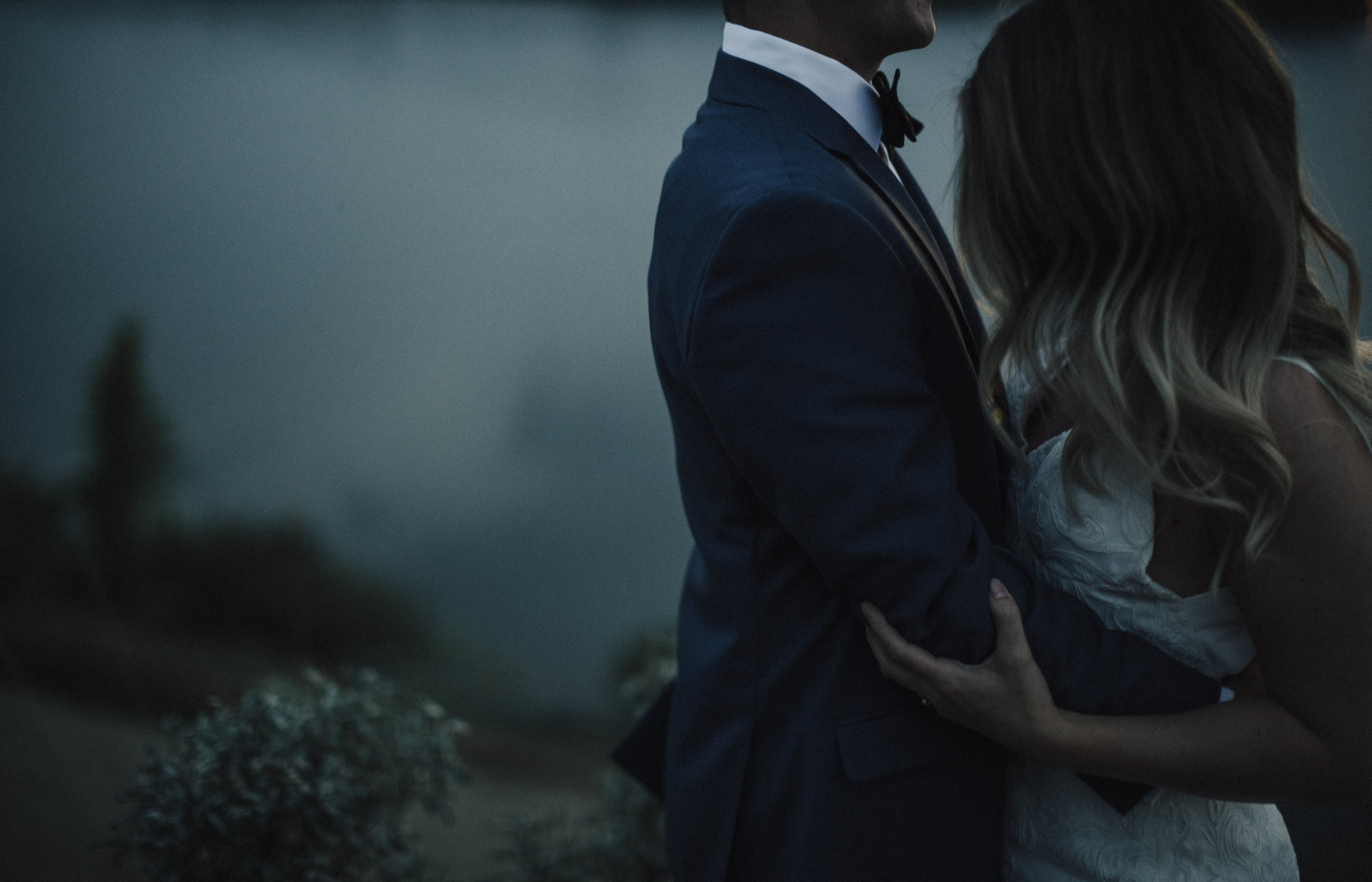 boho bride and groom cuddling in a moody evening setting deMo Photography