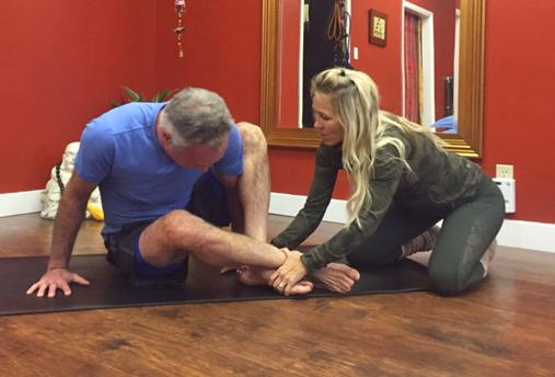 Lori teaching Scott an advanced arm balance.